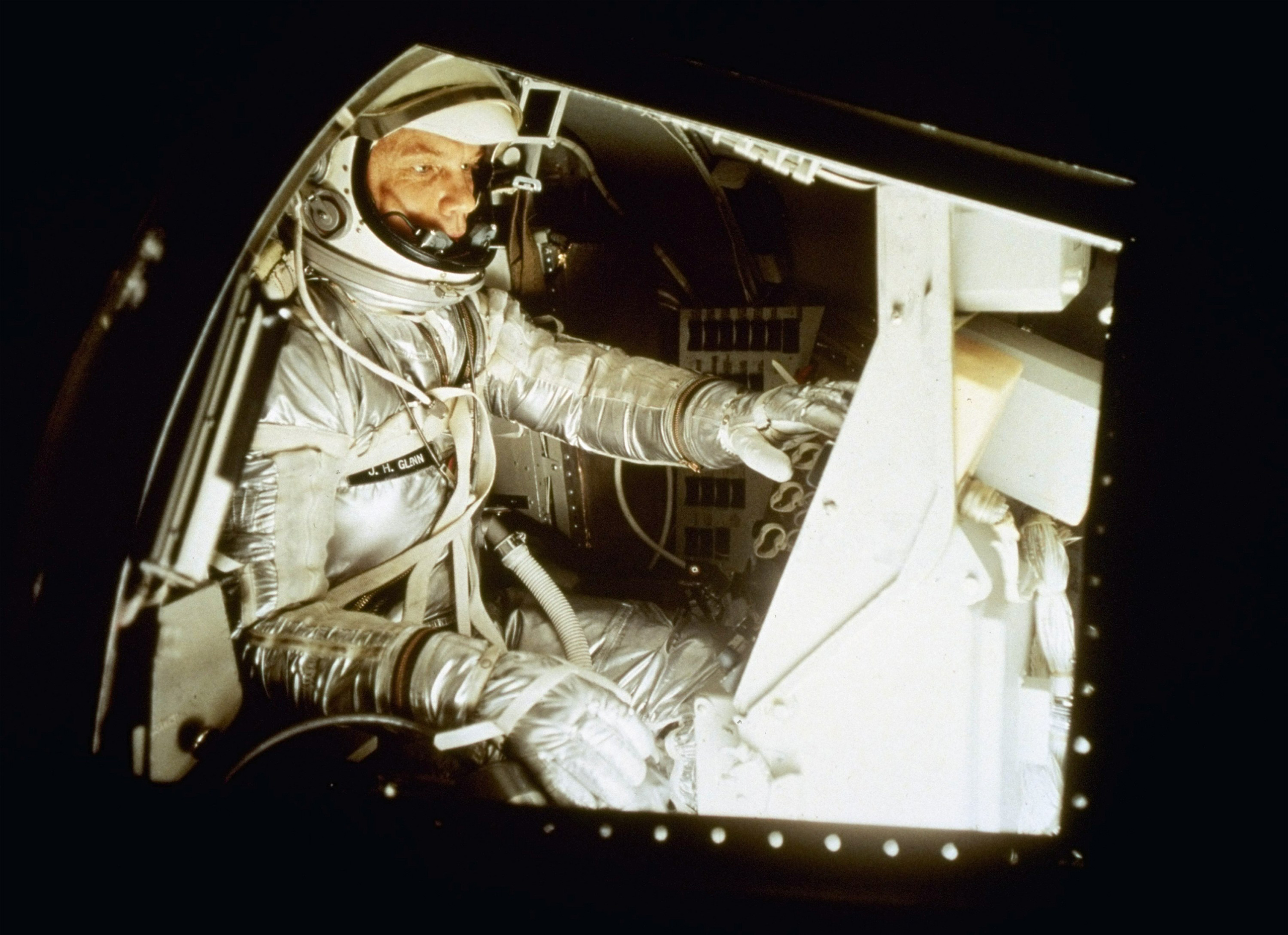 A Model Mercury Inside a training model of the Mercury spacecraft in 1961, Glenn familiarizes himself with the layout of the instrument panels. The capsule was so small, astronauts liked to say you didn't climb inside it — you simply put it on.