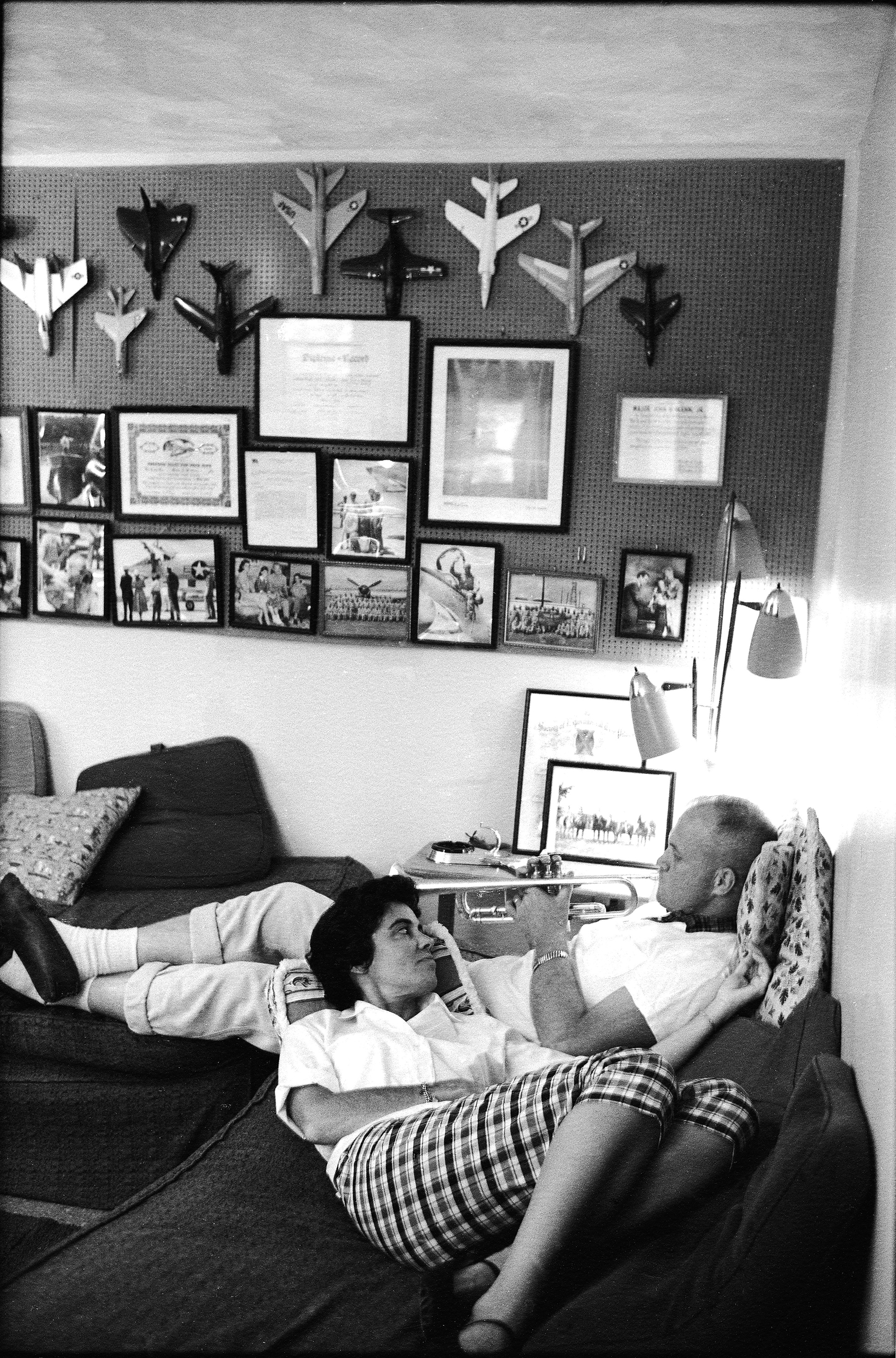 American astronaut John Glenn lies on a sofa and plays a trumpet for his wife Annie, who rests her head on a pillow on his lap, in Arlington, Va., 1961. The wall behind them holds a display of various models of jet aircraft, as well as a number of mounted photographs and certificates.