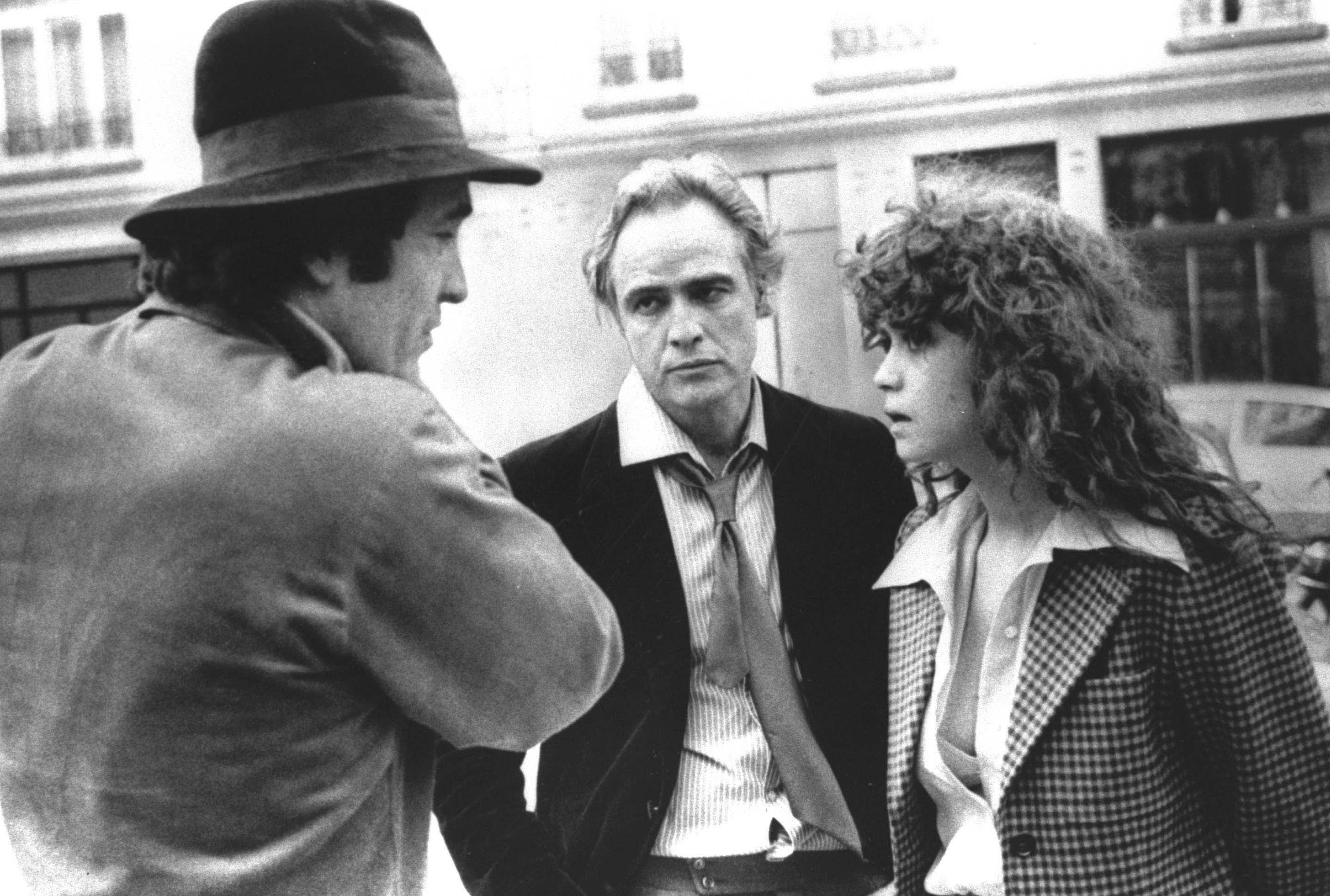 Director Bernardo Bertolucci, left, discusses a scene from  Last Tango in Paris  with leading actor Marlon Brando and actress Maria Schneider during location shooting in Paris.