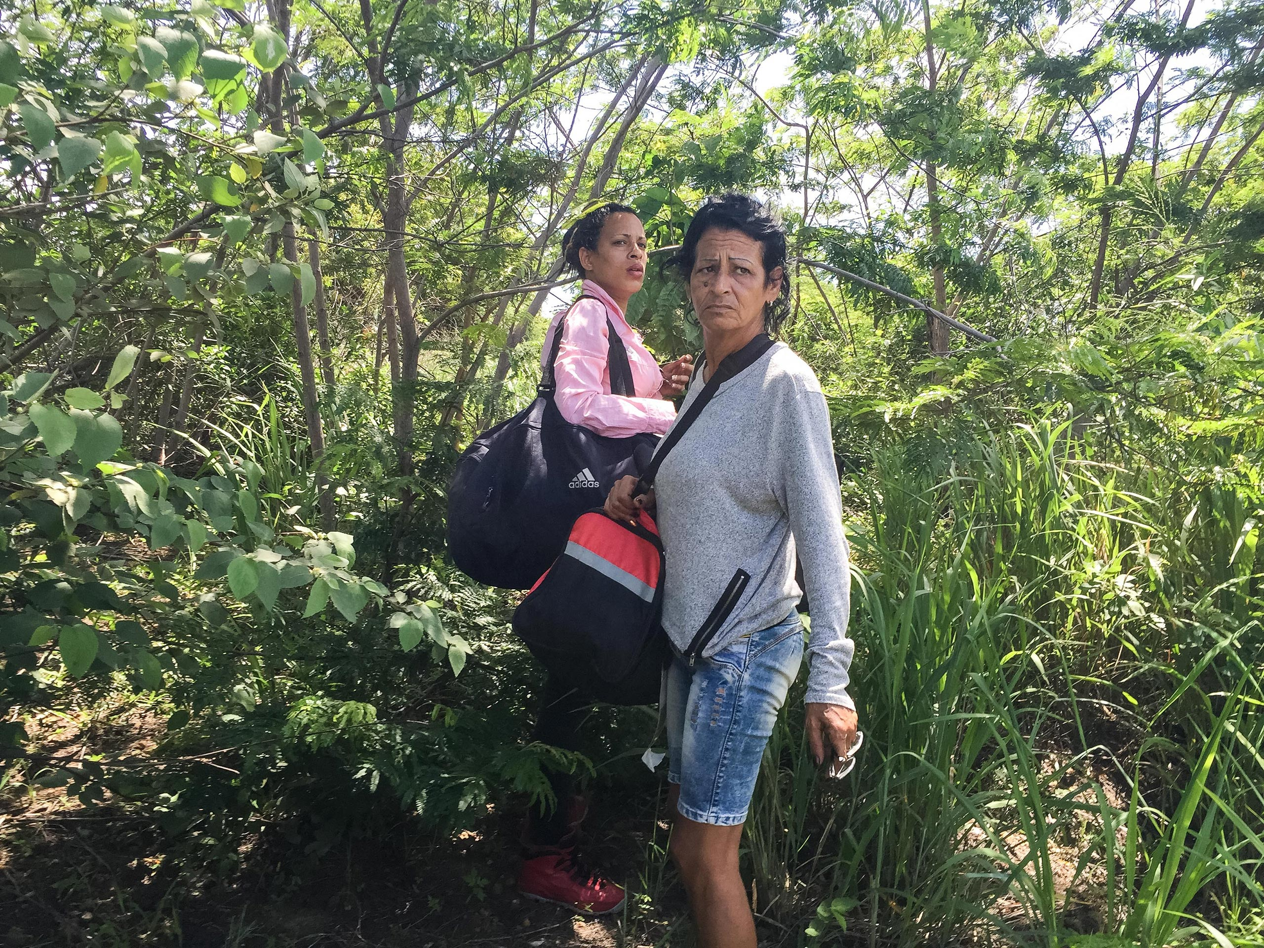 Marta, right, and Liset nervously watch for the signal to run to awaiting cars after crossing the border from Guyana into Brazil on May 14, 2016.From  The Long Way to America