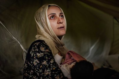 Taimaa Abazli, 24, holds her new baby Heln in their tent at the Karamalis camp in Thessaloniki, Greece, September 2016.