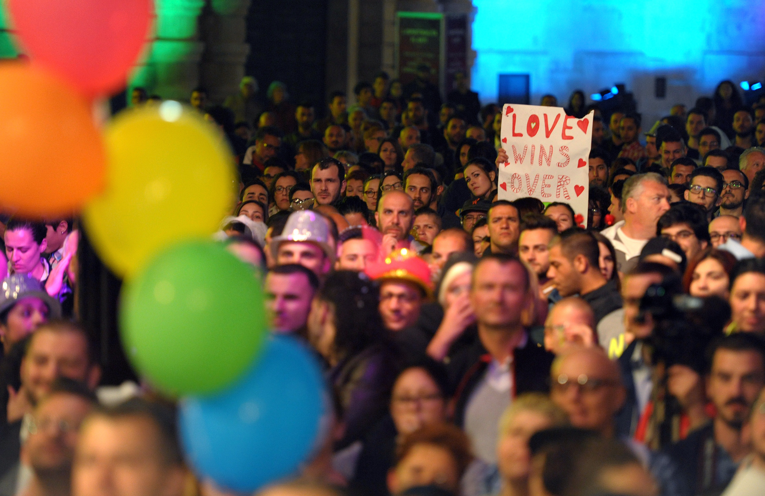 People gather to celebrate in Saint George's Square after the Maltese parliament approved a civil unions bill in Valletta on April 14, 2014. Malta's parliament approved the bill that grants marriage rights to homosexual couples, including the possibility to adopt children.