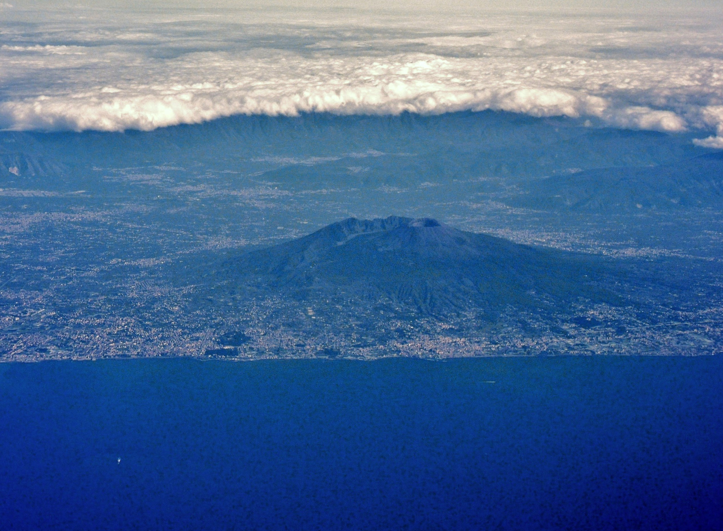 The view from the window of an airplane, took off from Capodichino International Airport, the Gulf of Naples and Vesuvius