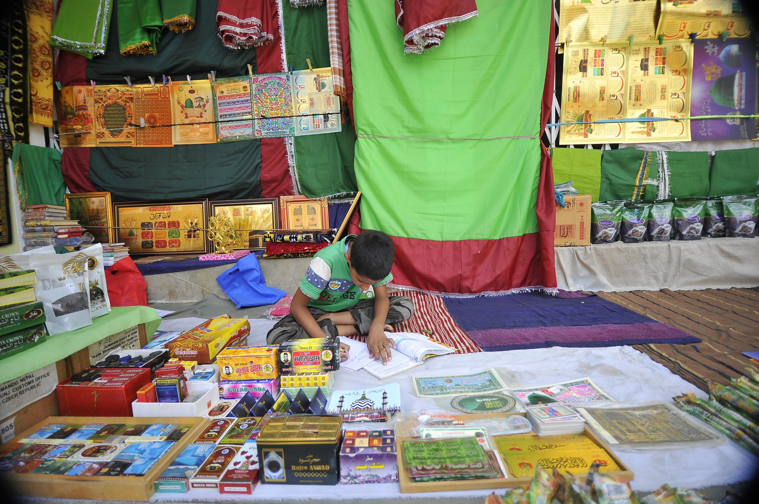Ghulam Raza, 11, does homework at the Ramadan Market of his father at Kashmiri Takiya Jame mosque at Kathmandu, Nepal, on June 9, 2016.