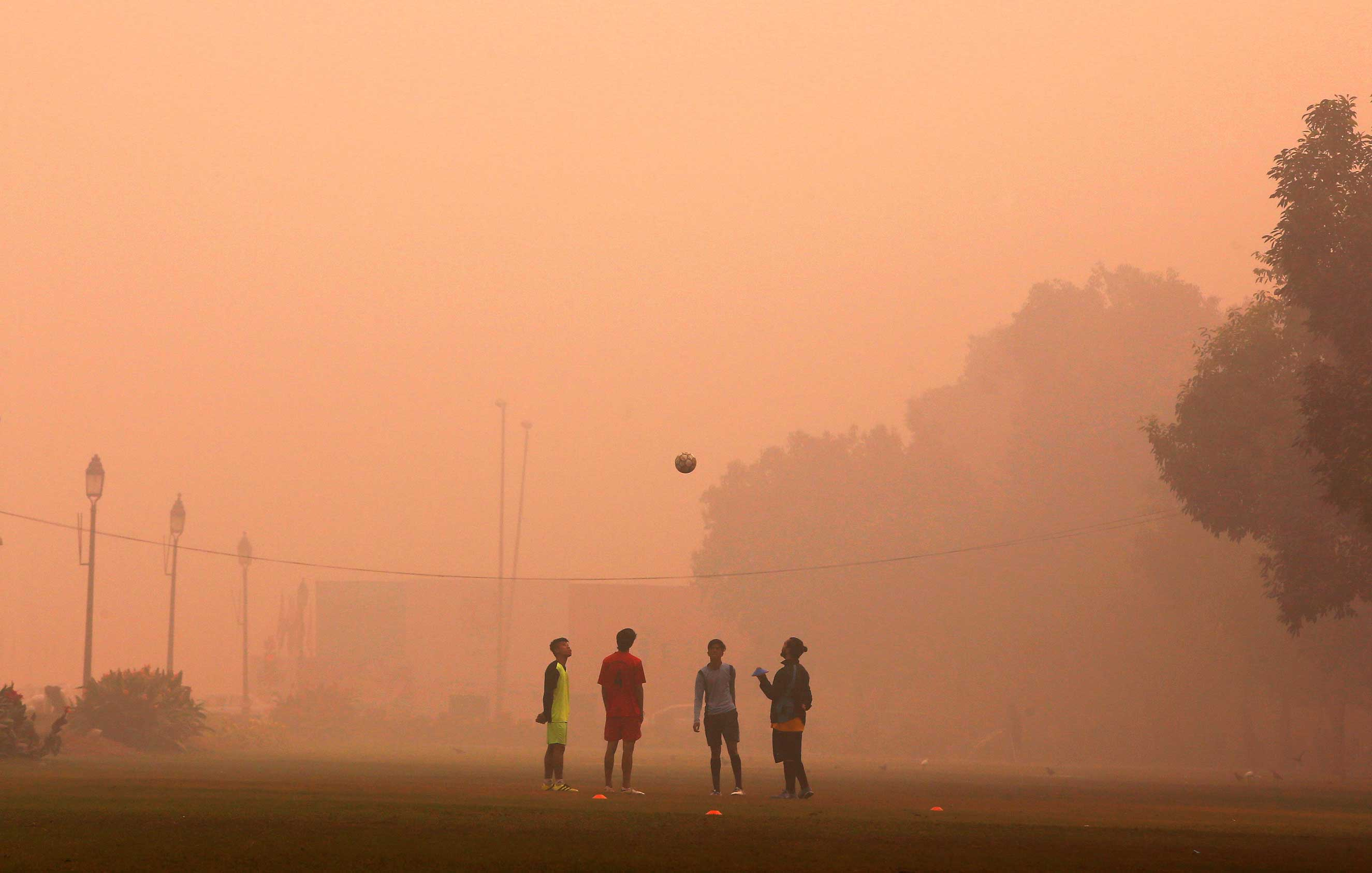 Children play on a smoggy day in New Delhi, where thousands die early from air pollution yearly