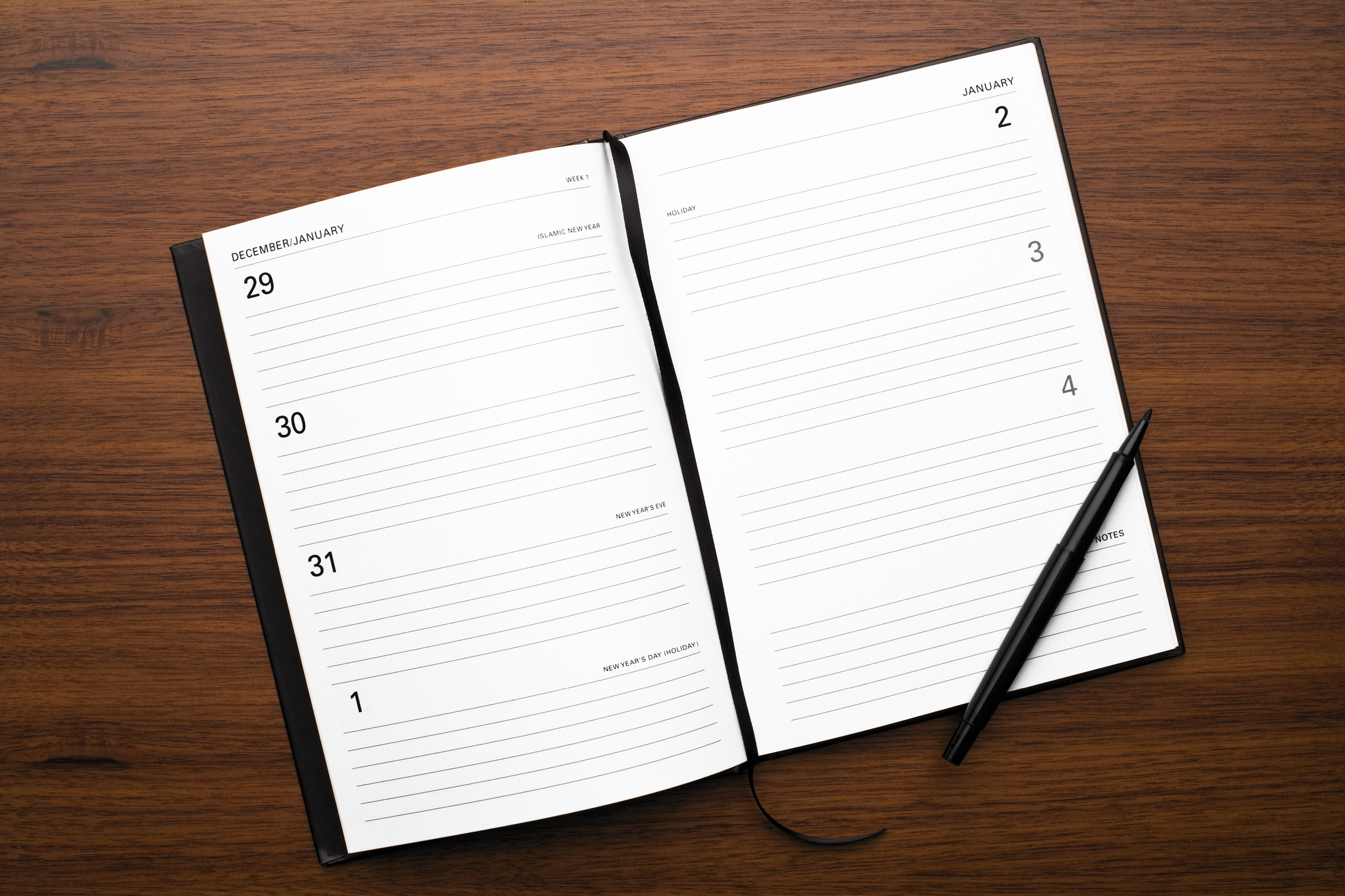 View from above of an open diary showing New Years Day on the page with a pen and on wood background