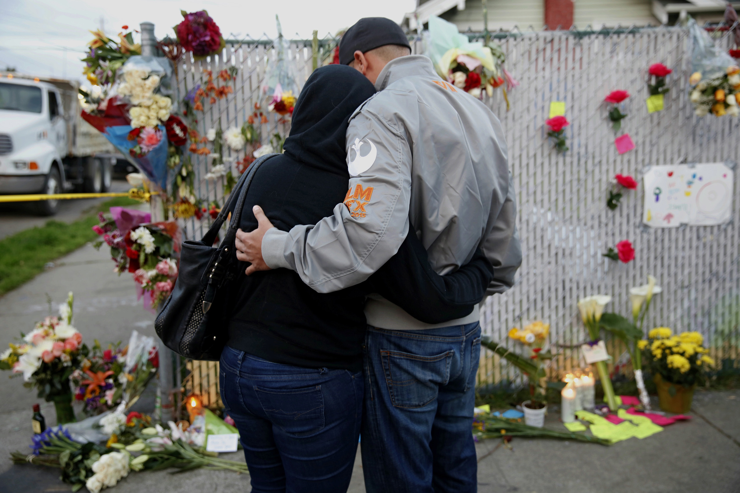 Mourners hug next to flowers near the site of the warehouse fire in Oakland, Calif., on Dec. 4, 2016.