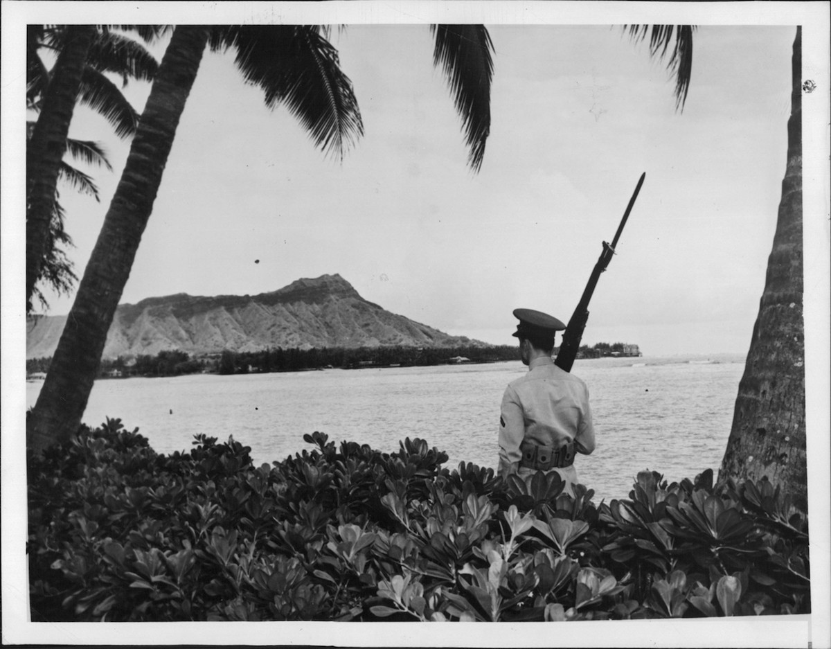 A sentry walks his post with a view of Diamond Head, marking Pearl Harbor U.S. Naval Base, in 1941.