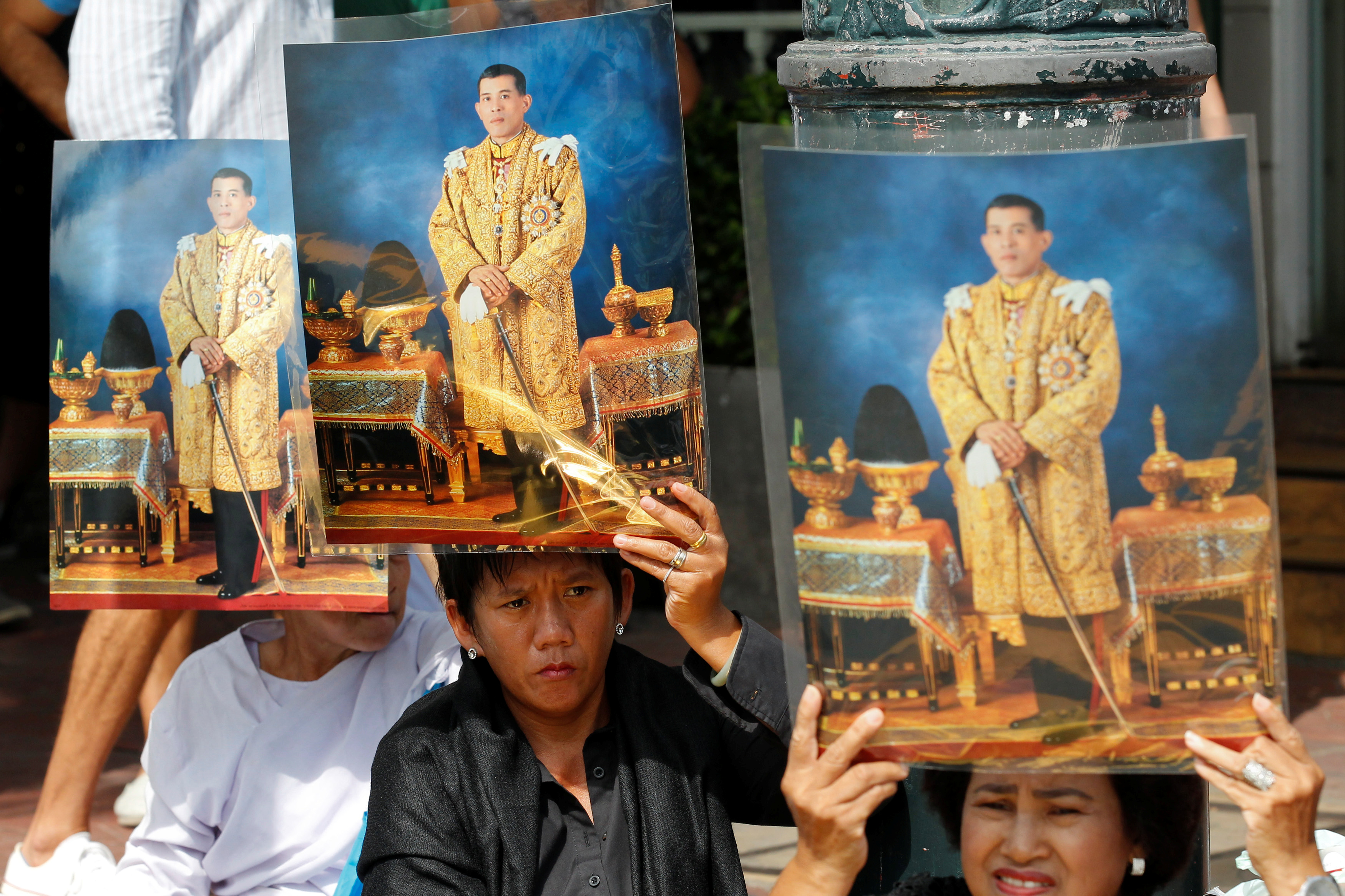 Well-wishers hold up pictures of Thailand's new King, Maha Vajiralongkorn, before he arrives at the Grand Palace in Bangkok on Dec. 2, 2016