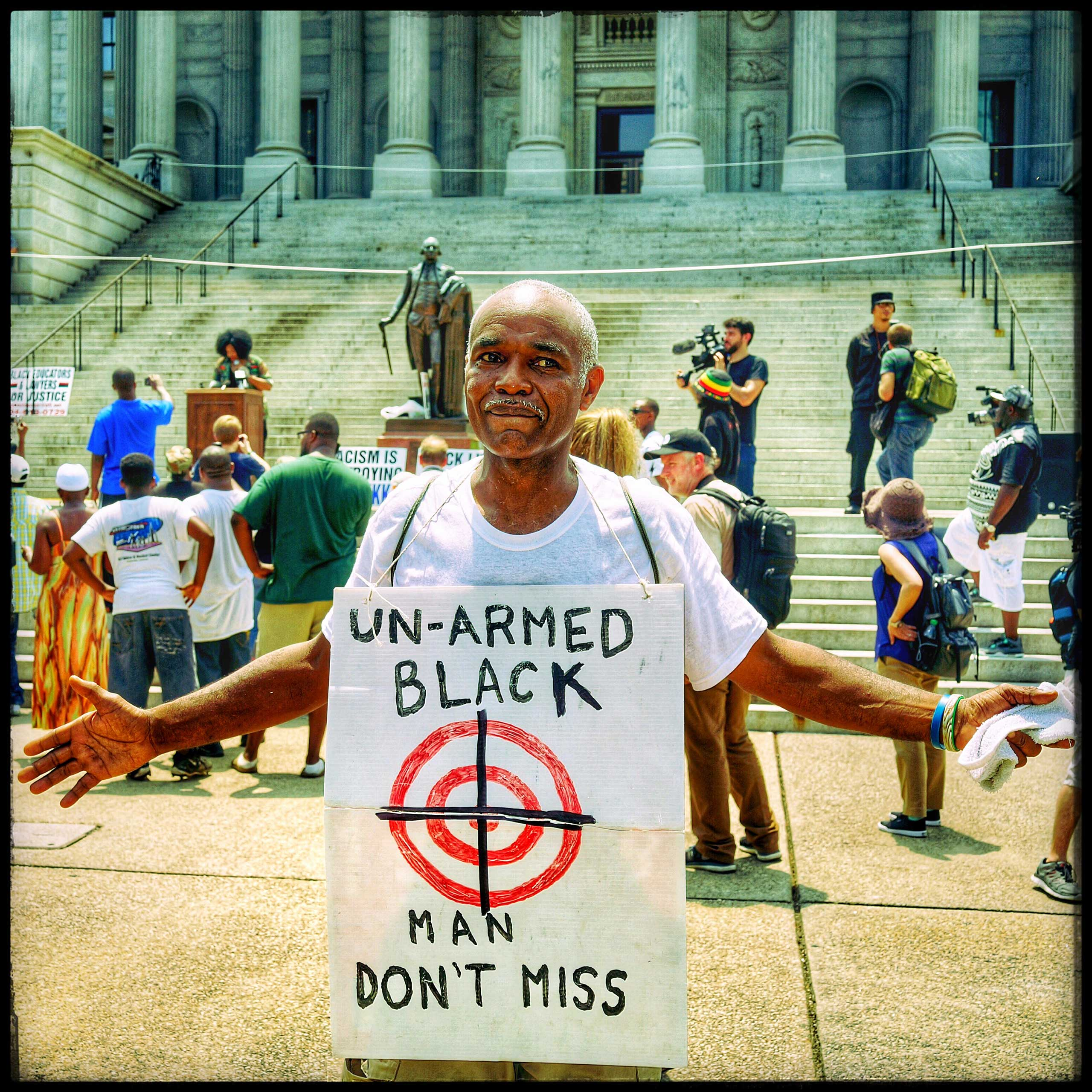 This man armed only with a sign around his neck demonstrates in front of the Capital Building in South Carolina. The event  was the staging of both a Ku Klux Klan and a Black Panther rally, both scheduled in the same area.