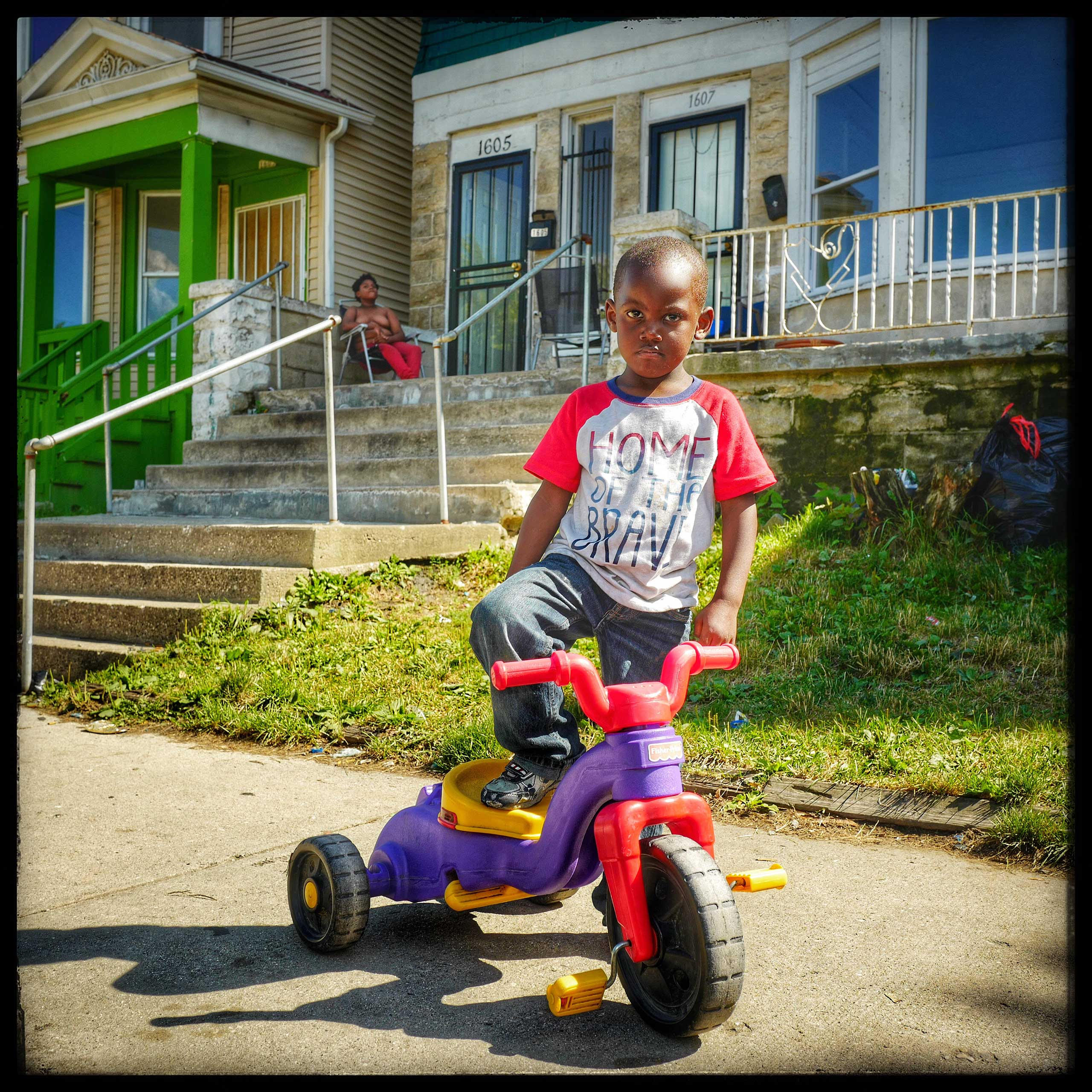Budd stands on his bike proudly in the zipcode that is said to be the worst in all of America.