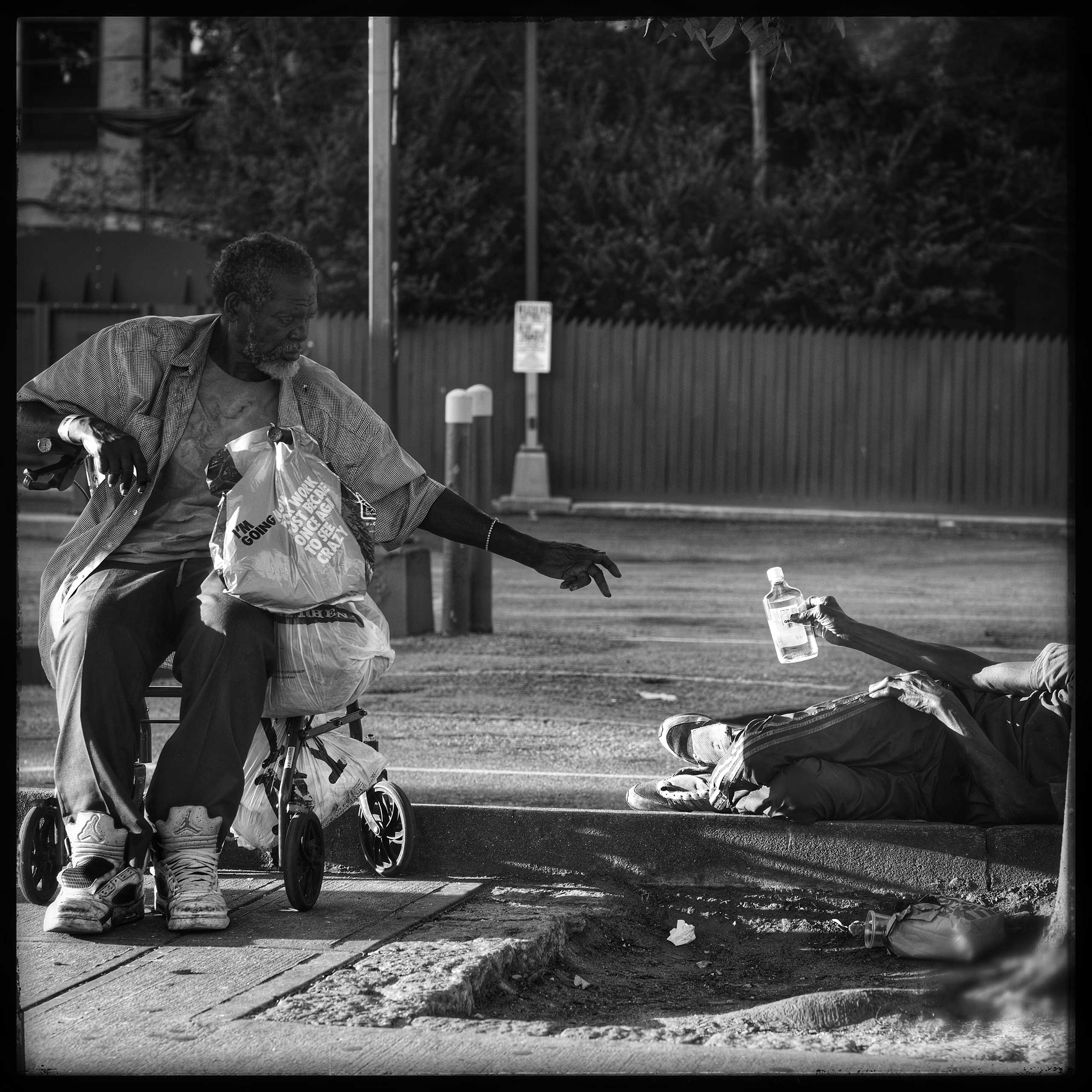 Sharing a drink with a friend. Two elderly gentlemen pass the time by drinking and sharing moments together on Fulton Street in Brooklyn.