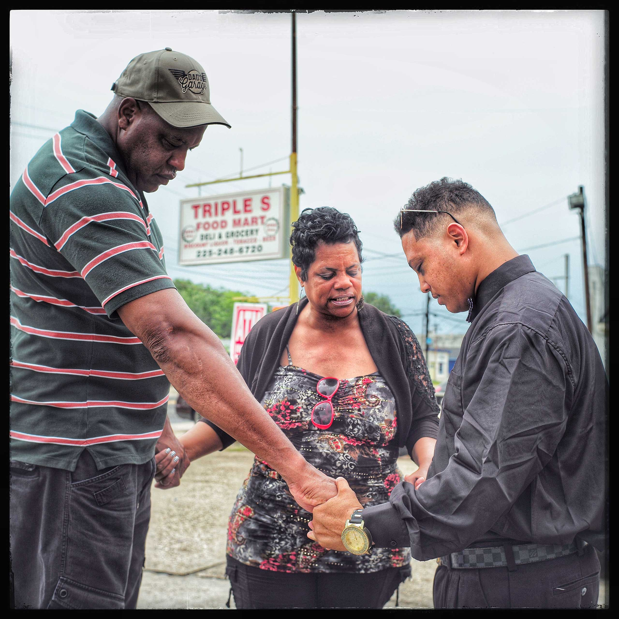 Praying for a successful meeting with 24 year old javier Dunn (far left). Dunn, who was arrested for protesting the Alton Sterling shooting by the Baton Rouge Police Department, was told he had to go see his parol officer as a condition of his release. Here, two community pastors pray with him before his meeting.