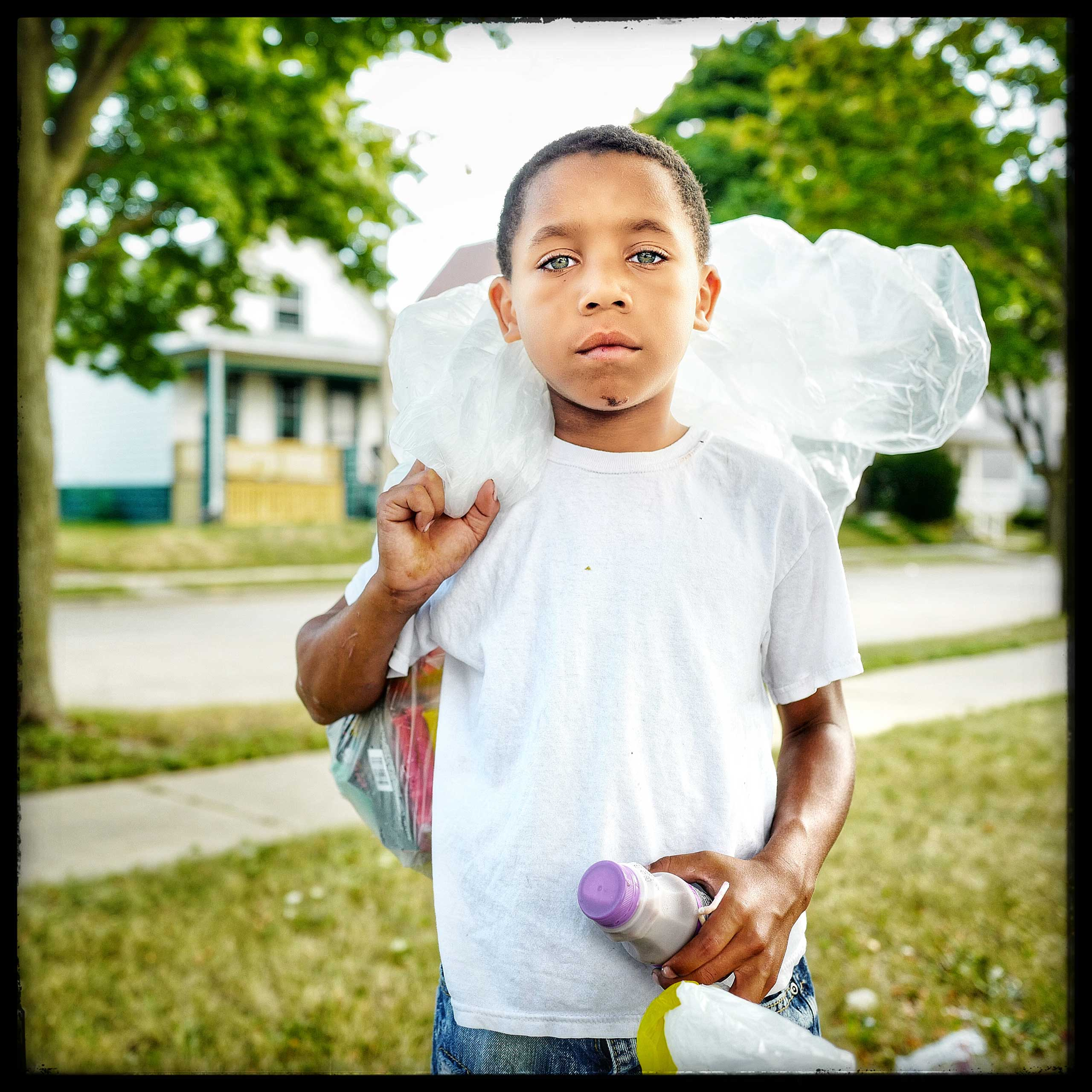 10 year old Darian after stopping at a Salvation army truck where he was given a ham sandwich, some fruits and a bottle of milk. Residents of the zipcode 53205 in Milwaukee often meet the truck around 1 pm where they are given a meal.