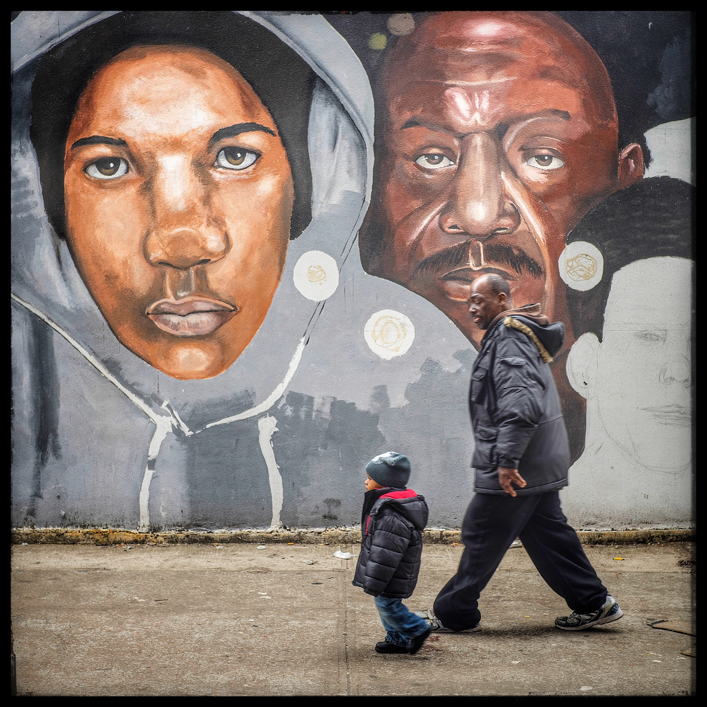 A father and son reflected against the portrait of Trayvon Martin's face on the mural in Brooklyn.