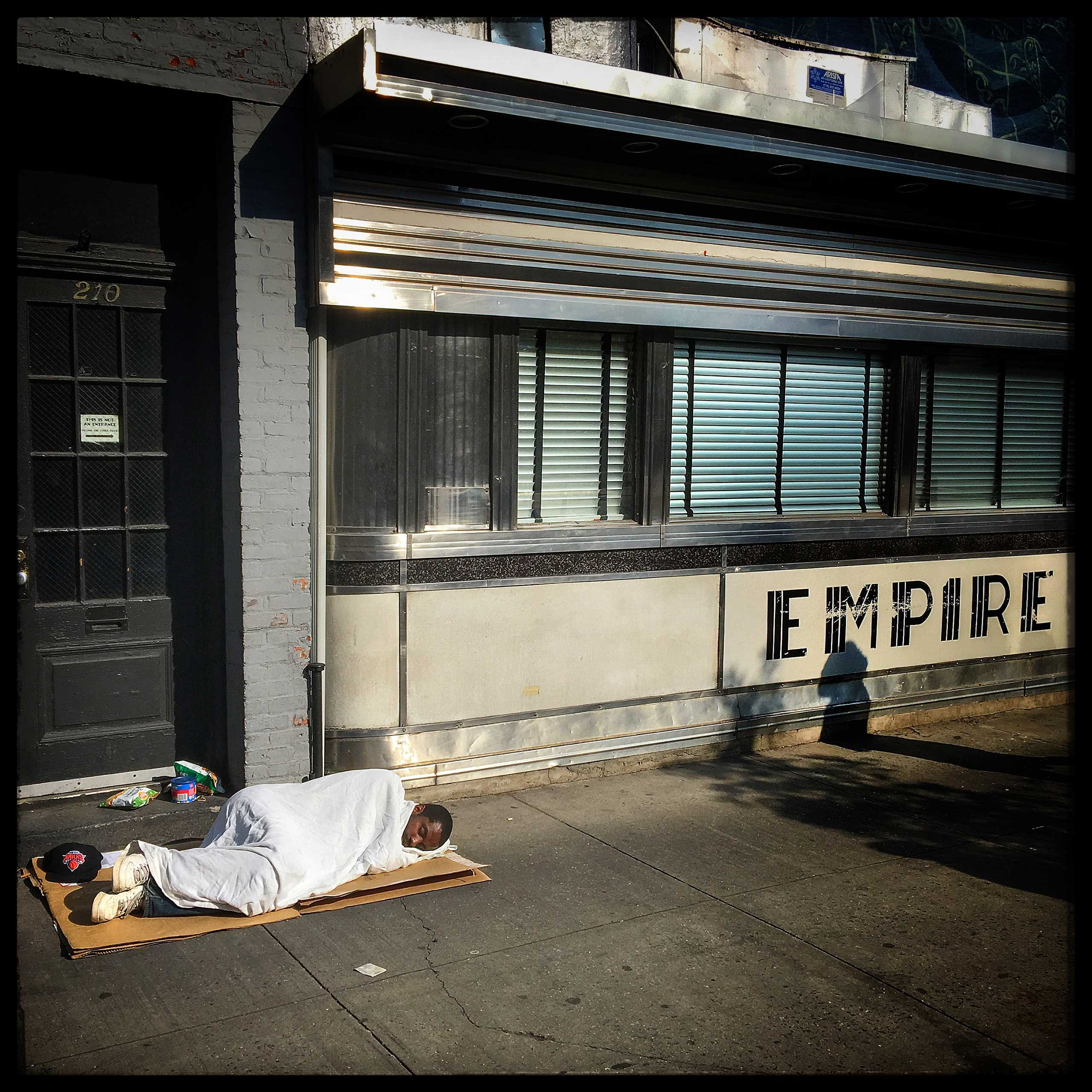 A man sleeps on the streets of Manhattan, a city touted to be one of the most popular cities in the world.