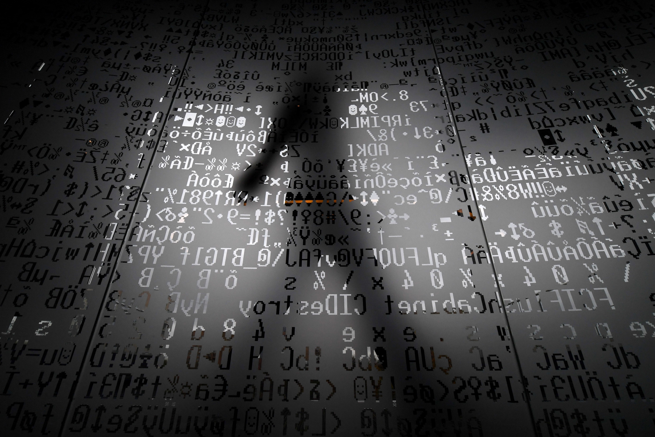 An employee walks behind a glass wall with machine coding symbols at the headquarters of Internet security giant Kaspersky in Moscow on Oct 17, 2016.