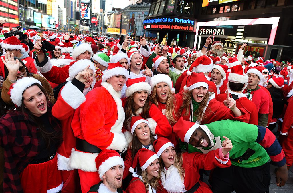 People dressed as Santa Claus and Mrs. Claus pose in Times Square as they gather for the annual Santacon festivities on Dec. 13, 2014 in New York City.