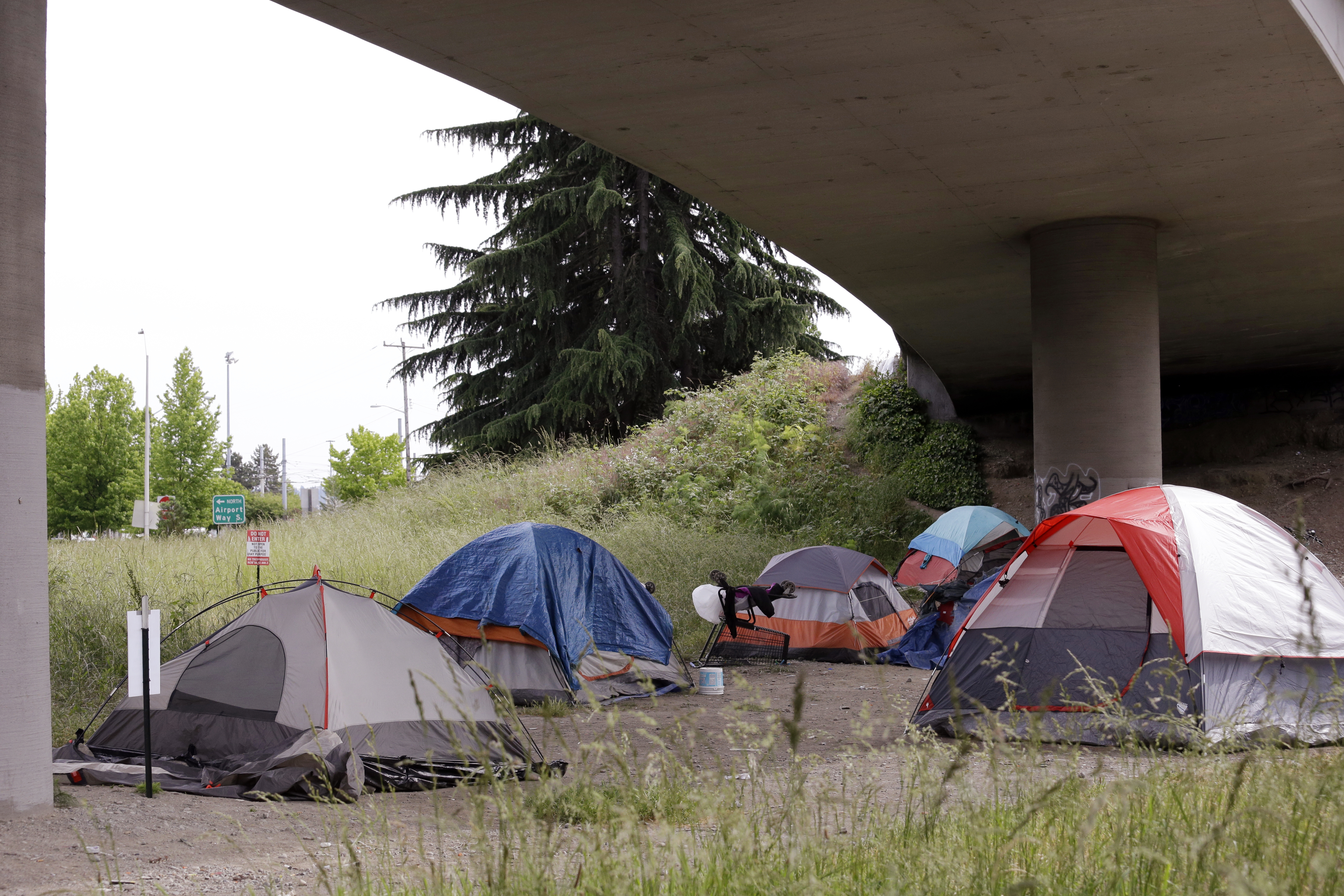 Tents line a small green space below Interstate 90 and a short walk to a homeless area known as the Jungle, May 17, 2016, in Seattle.