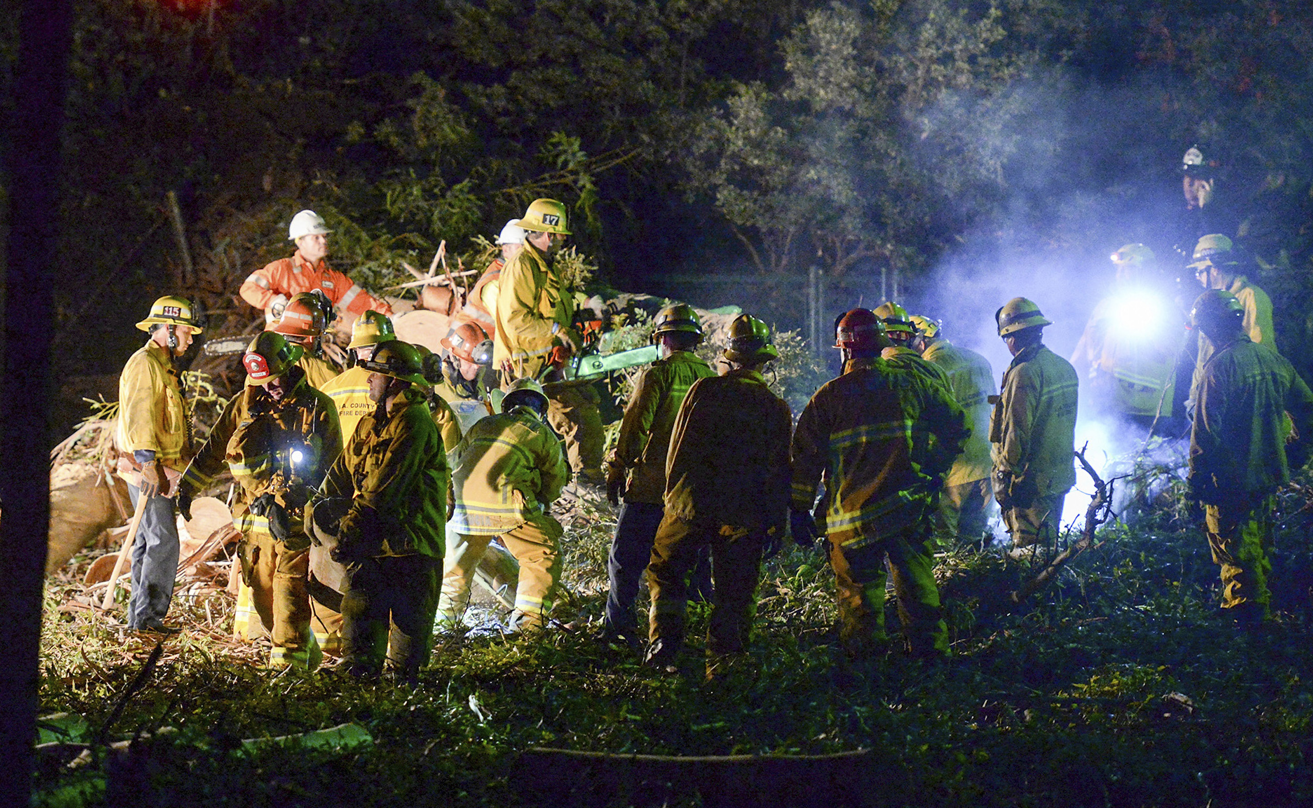Los Angeles County Fire Dept. firefighters work at the scene where a large tree fell on a wedding party in Whittier, Calif., Saturday, Dec. 17, 2016.