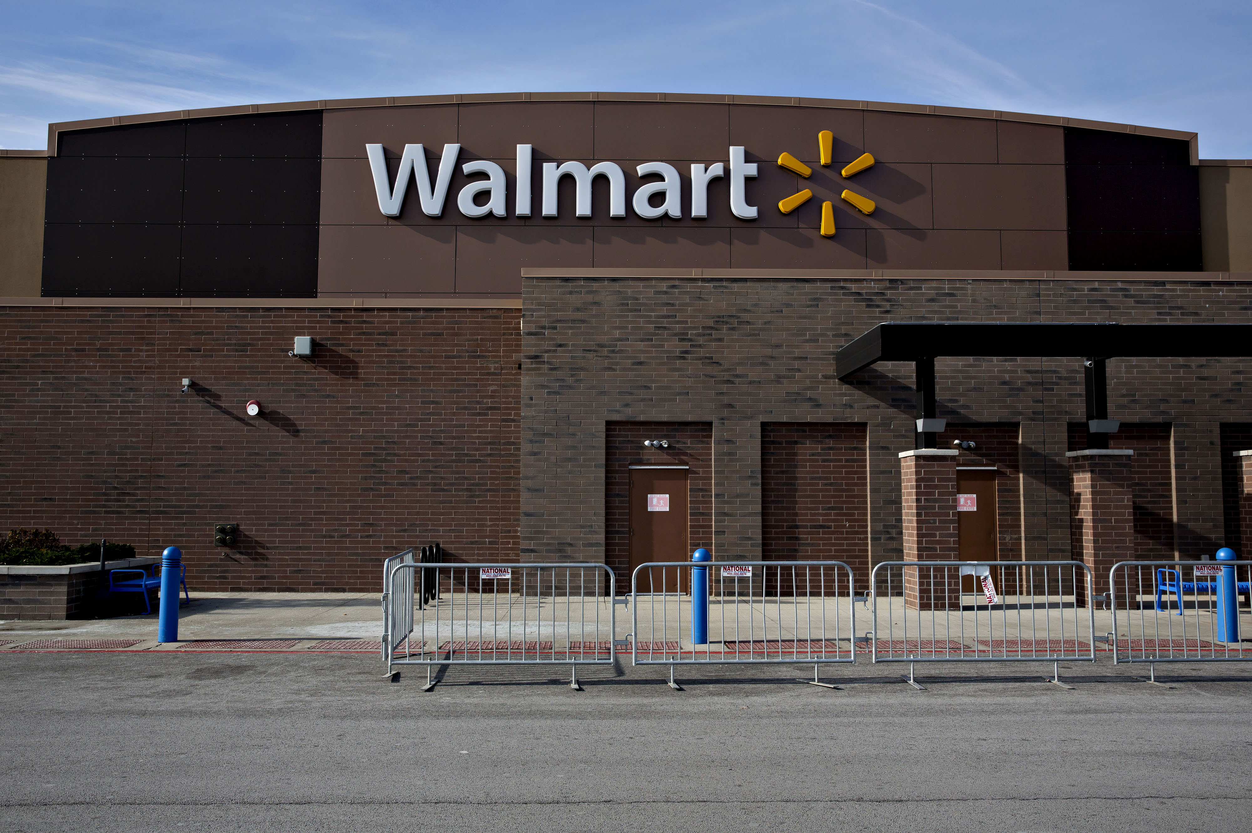 Temporary security fencing sits outside a Wal-Mart Stores Inc. location in Chicago, Illinois, U.S., on Wednesday, Nov. 25, 2015.