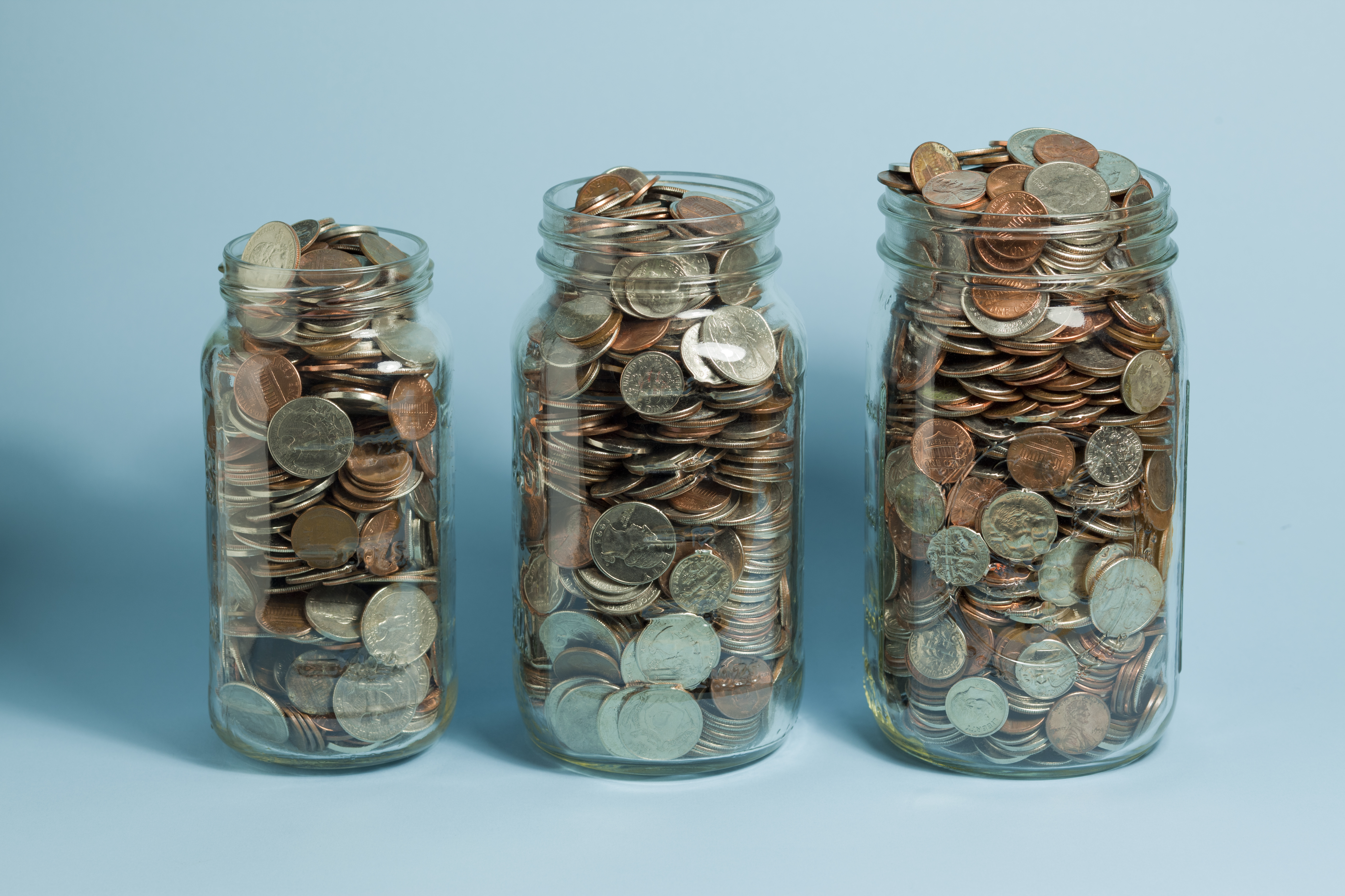 Three Mason jars filled with American coins. The jars get bigger left to right.