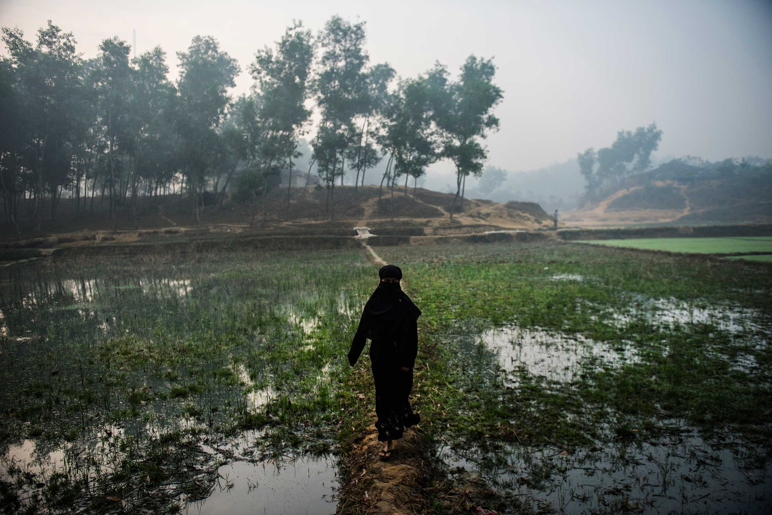 A Rohingya woman walks around the perimeter of the Kutupalang informal camp for unregistered Rohingya refugees from Myanmar in Teknaaf Bangladesh, Jan. 11, 2016.  Beside the Kutupalang camp is a registered camp of 15000 refugees, and the makeshift camp has grown over the years to approximately 40000 unregistered refugees. The inhabitants are provided with no services: there are rudimentary, unsanitary outdoor latrines, raw sewage streaming through the camp, no food distributions, and lack of medical care.