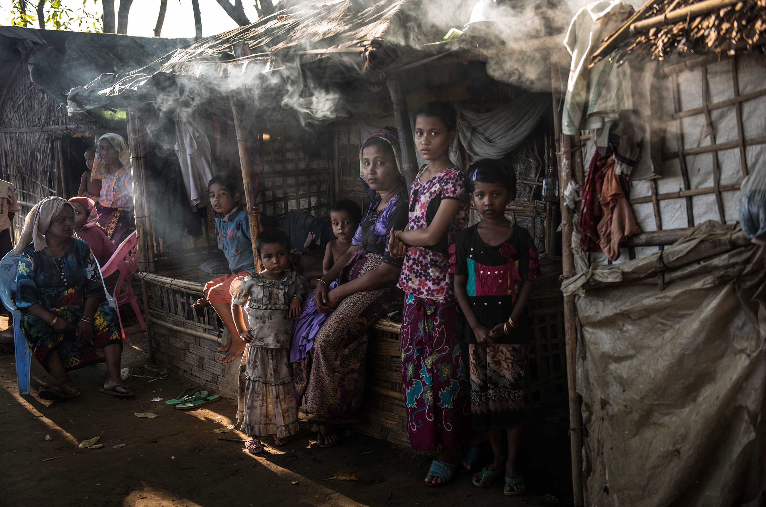 The Rohingya, Burmese Muslims, live in the Thay Chaung camp for the Internally Displaced outside of Sittwe, which houses nearly 3000 people, Nov. 23, 2015.   Mother with twin boys under cooking smoke: Kamila Begam 25, has five children and are from Than Taw Lee, about five miles away from the Thay Chang camp where they are currently living. Standing by smoke: Halima Katu, 10, flowered top, and Khotiza Kata, 6, black top with red and green flowers.