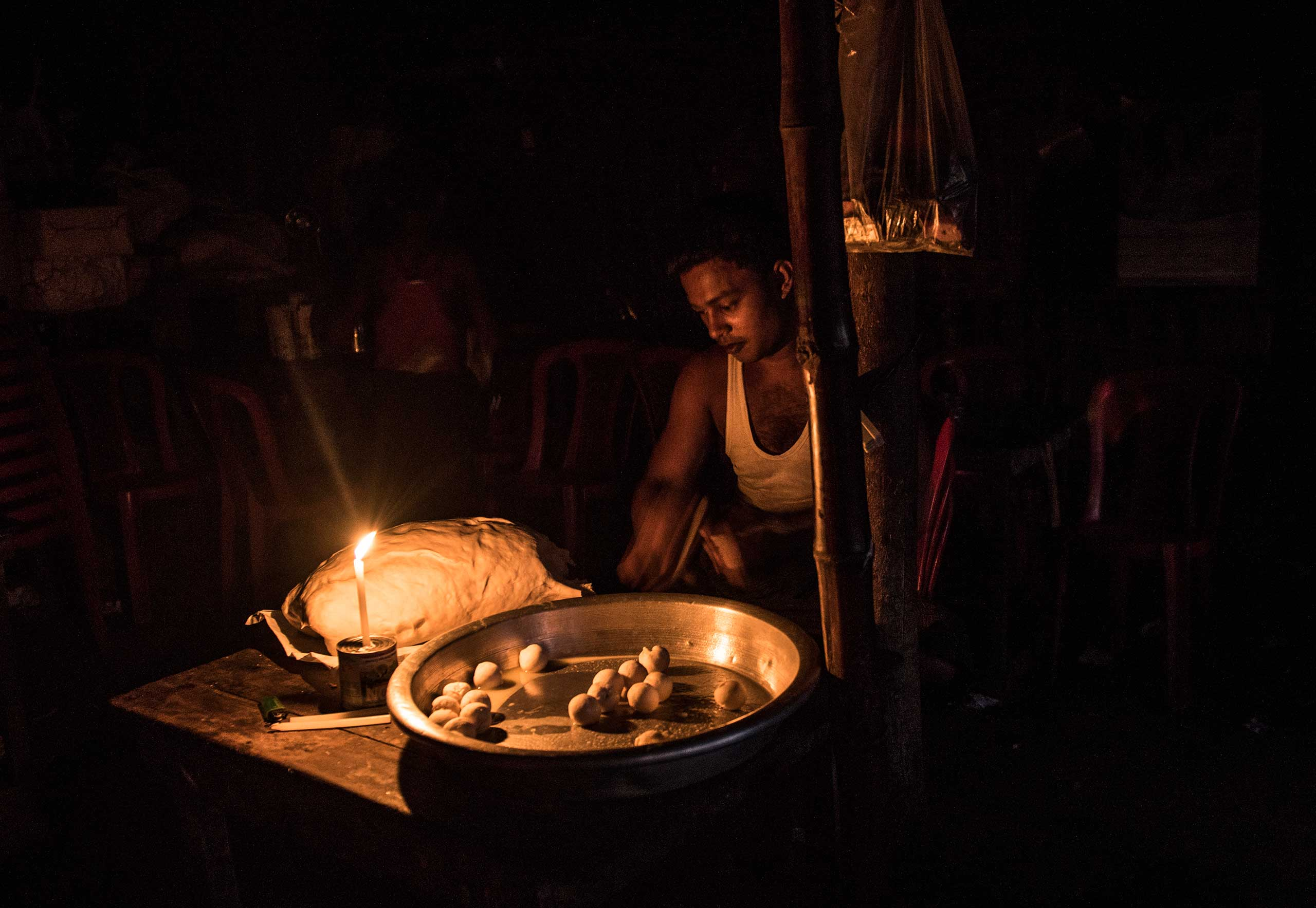 A Rohingya man, Burmese Muslims, sells food at a stall at night in the Thay Chaung camp for the Internally Displaced outside of Sittwe, which houses nearly 3000 people, Nov. 23, 2015.