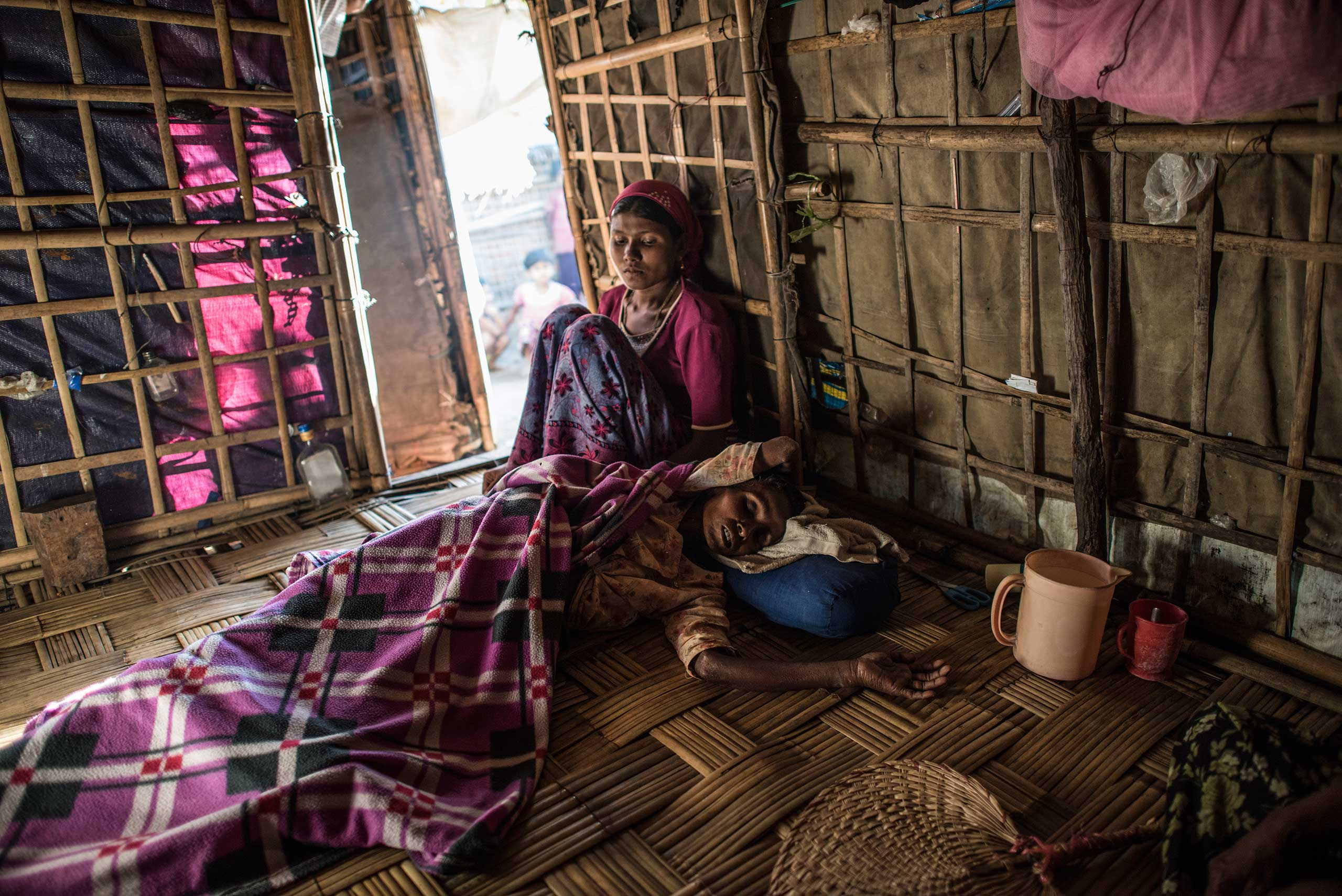 """Sumeir, 35, is comforted by her daughter as she lies semi-conscious on the floor of her family's home a few days after surgery at the Sittwe hospital, outside of the Thay Chaung camp, Sittwe, Myanmar, Nov. 24, 2015.  For many years, Sumeir suffered from excruciating stomach pain. She went to the That Kay Pyin Emmergency hospital within the IDP camp, and was referred to Sittwe hospital, outside of the camp.  She was operated on a few days prior in Sittwe, and quickly discharged and returned to the IDP camp at Thay Chaung, allegedly without post-operative care, information about her condition, and without medication for healing. She passed away the day after this picture was taken.   """"We are not dogs, we are not cows, we are people. There is a difference in how they treat us. They leave us to our own devices."""" In the hospital, there is a lot of discrimination,"""" Azumeir says.  The Rohingya in Myanmar are routinely denied proper medical care—within the camps around Sittwe, the only  available medical care is at the emergency hospital, and both medical staff and prescription drugs are limited. Anyone with a serious condition may be referred to Sittwe, but the Rohingya often don't trust government hospitals, and do not have the money to pay for meals and any additional expenses outside of treatment.  Lack of medical care is one of the biggest concerns for the Rohingya."""