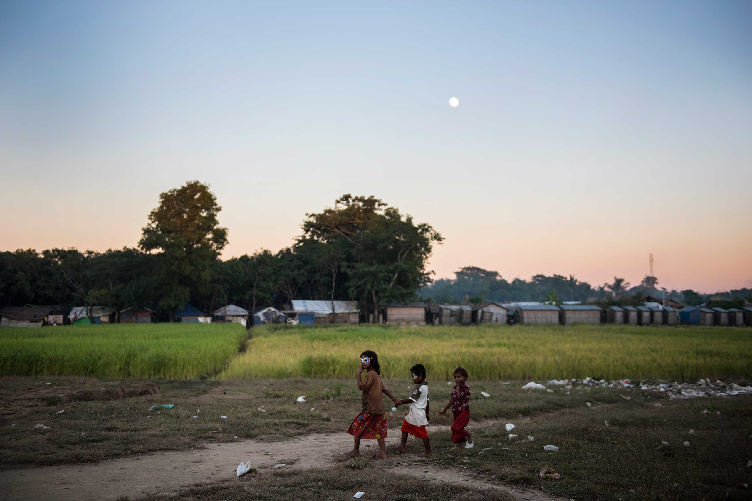 Rohingya children walk through the Thay Chaung camp at dusk for the Internally Displaced outside of Sittwe, which houses nearly 3000 people, Nov. 23, 2015.