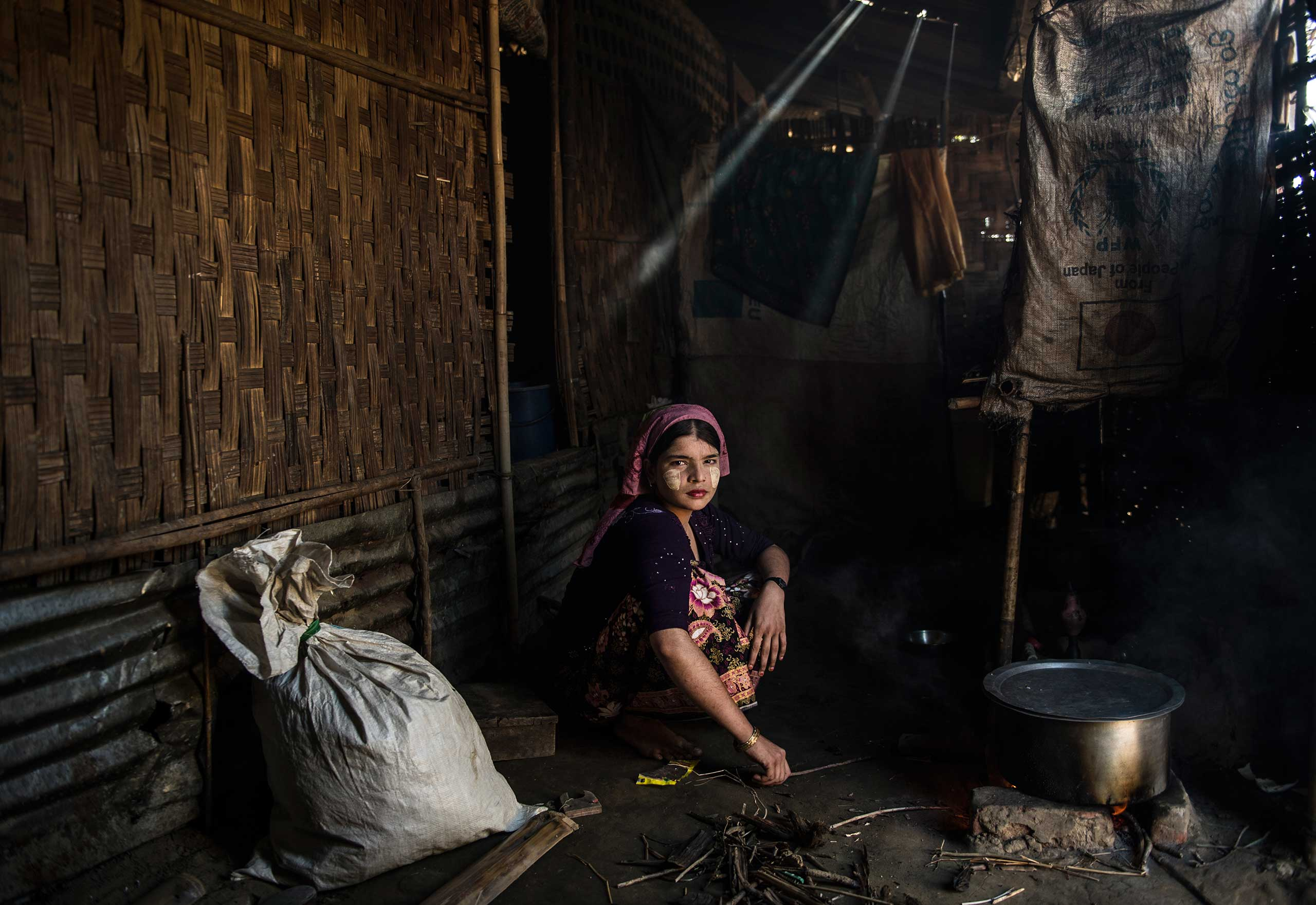 Say Tha Mar Gyi camp for Internally Displaced Rohingya. Aisha Begum, 18, cooks in her family home in the camp, Nov. 26, 2015. Aisha is married, but her husband left her less than a year ago to go live with his family again.