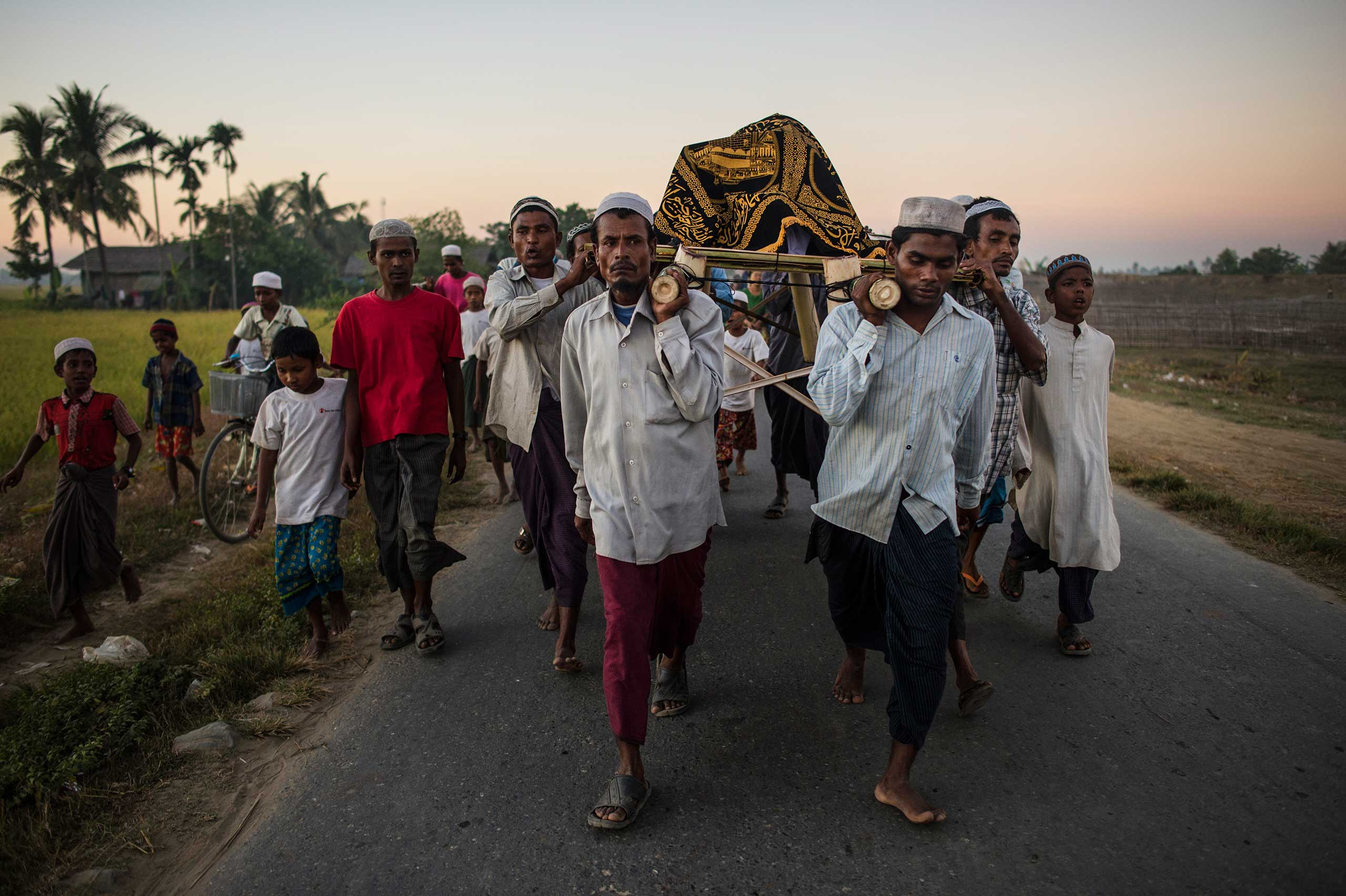 Rohingya men,  Burmese Muslims, carry the body of an elderly man who died of natural causes through the Thay Chaung camp for the Internally Displaced outside of Sittwe, which houses nearly 3000 people, Nov. 23, 2015.