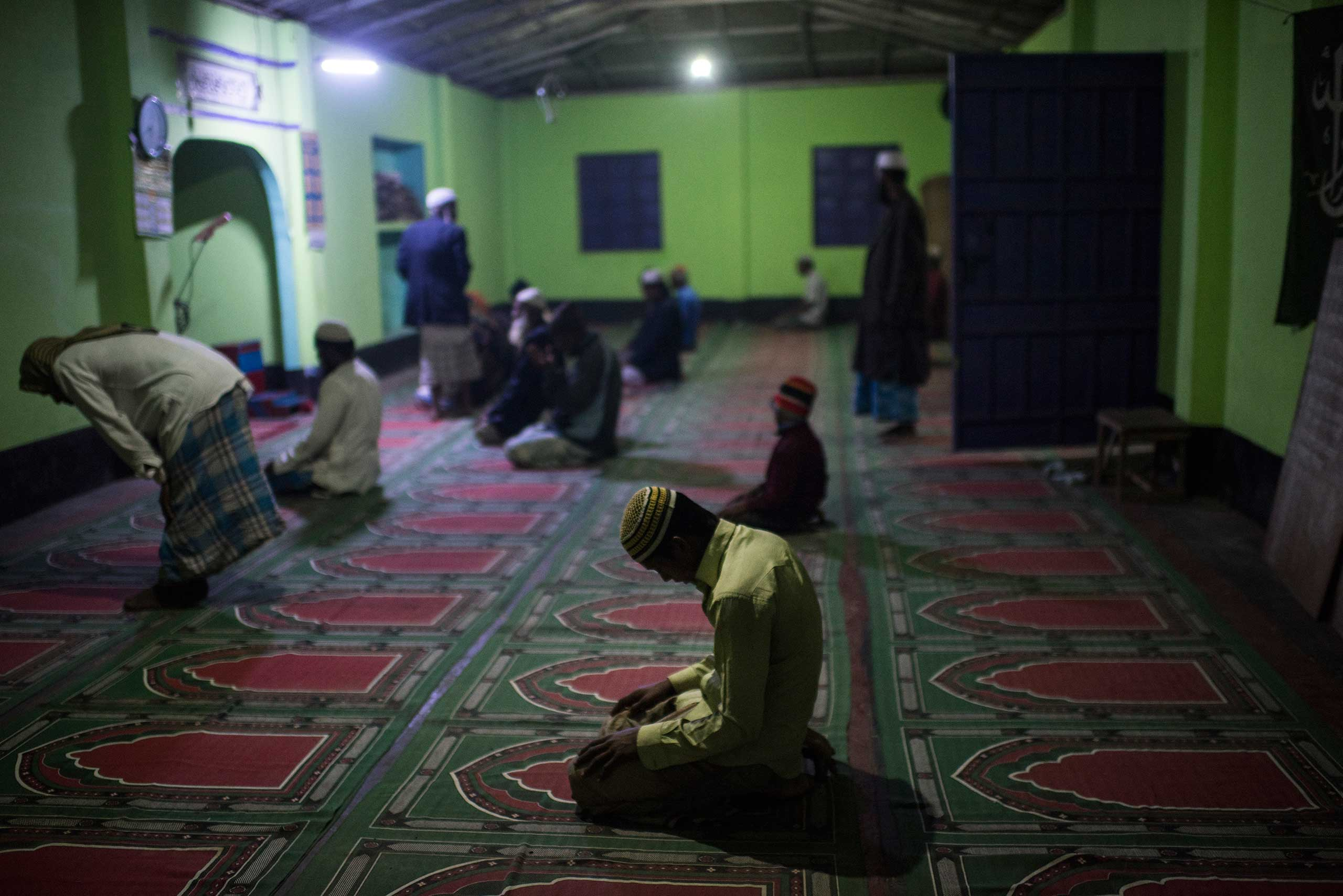 Rohingya men pray at a mosque in Shamlapur, a Rohingya settlement, outside of Cox's bazaar. While there are very few opportunities for Rohingya children to go to school, most children do study the Koran at the local madrassa with the Imam of the community, in  Bangladesh, Jan. 16, 2016. The Rohingya are systematically marginalized, and forced into formal and makeshift camps across Bangladesh and Myanmar.