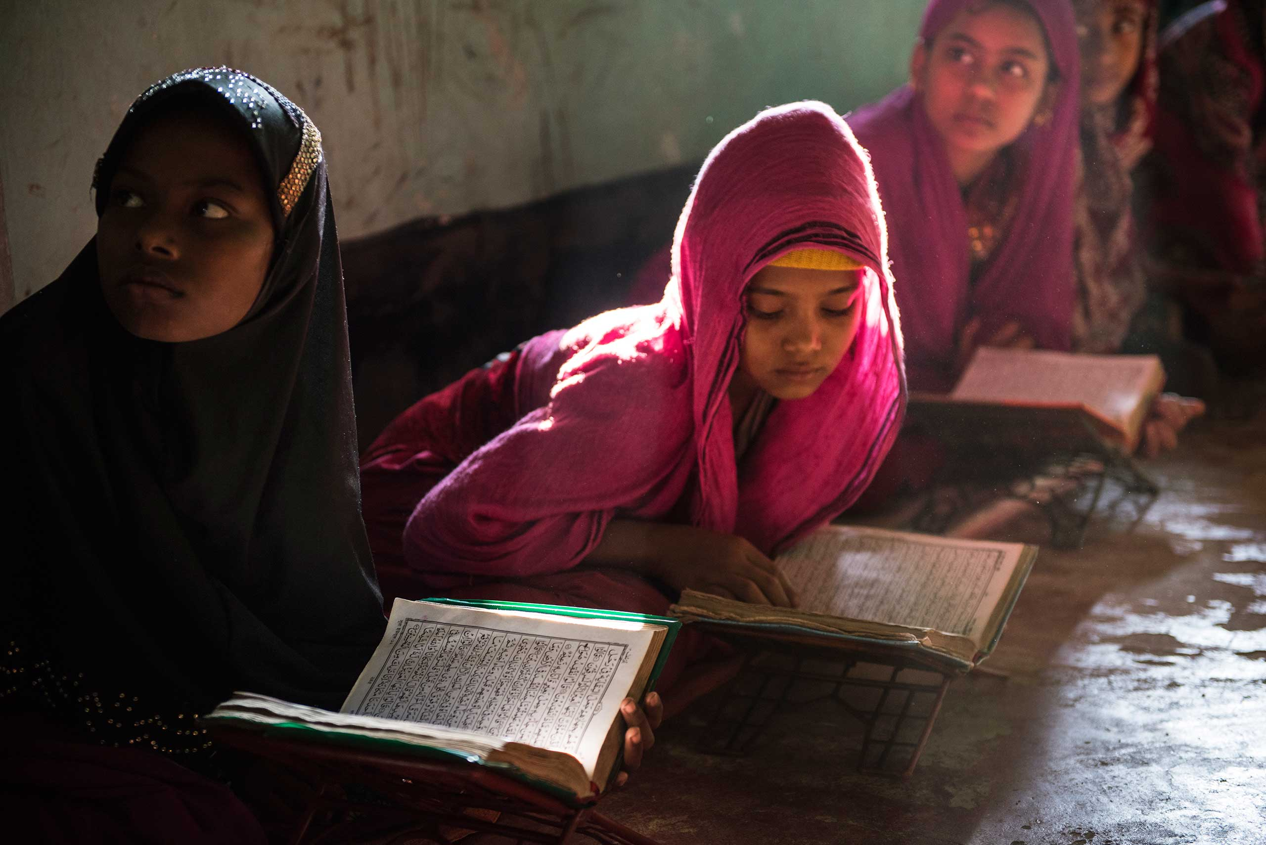 Sitara, 8, left, and Shahana, 10, right, read the Koran at a madrassa in a mosque in Shamlapur, a Rohingya settlement, outside of Cox's bazaar. While there are very few opportunities for Rohingya children to go to school, most children do study the Koran at the local madrassa with the Imam of the community, in  Bangladesh, Jan. 16, 2016.