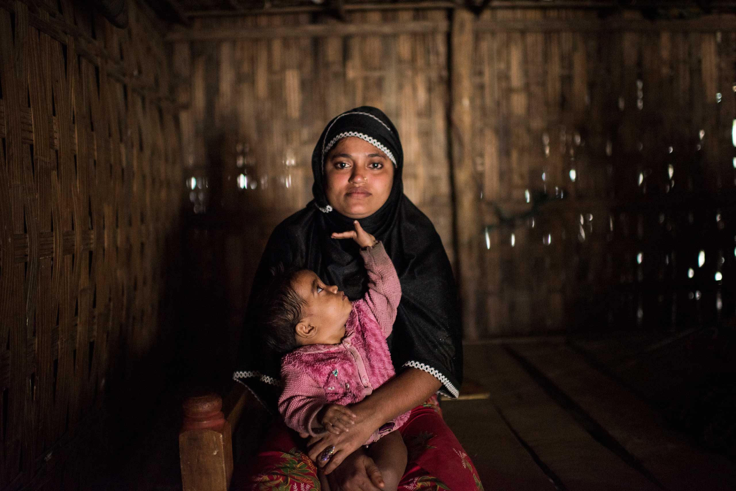 Rohingya woman Shahda Begham, 25, poses for a portrait with Jannatara, 2, one of three daughters, in a home in an informal settlement in Shamlipur, in Bangladesh, Jan. 10, 2016.   Shahda was living in Mongdo with her husband when their village was overrun by violence. Military came in and shot her husband--killing him--and took her and several other women into the forest and raped her repeatedly.    The military beat us; if somebody didn't want to go, it was rape. They tortured me in the forest; even when they pulled us from the bush they beat us.   She later fled to Bangladesh with her three children. The Rohingya are systematically marginalized, and forced into formal and makeshift camps across Bangladesh and Myanmar. They often occupy hard labor jobs, like riding cycle rickshaws, working in the ice factories, fishing, and manual labor jobs they pick up daily.