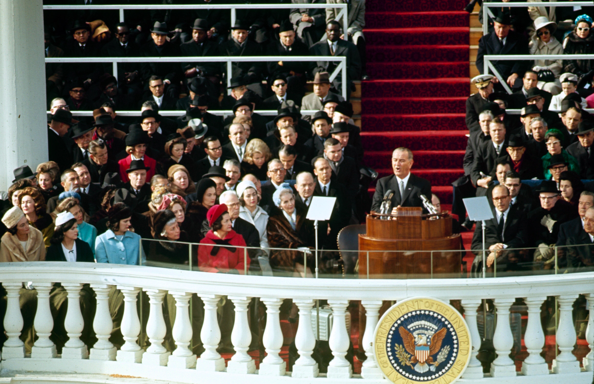 Lyndon Johnson giving the inaugural address at his  inauguration. First Lady, Lady Bird Johnson is seated to his right, 1965.
