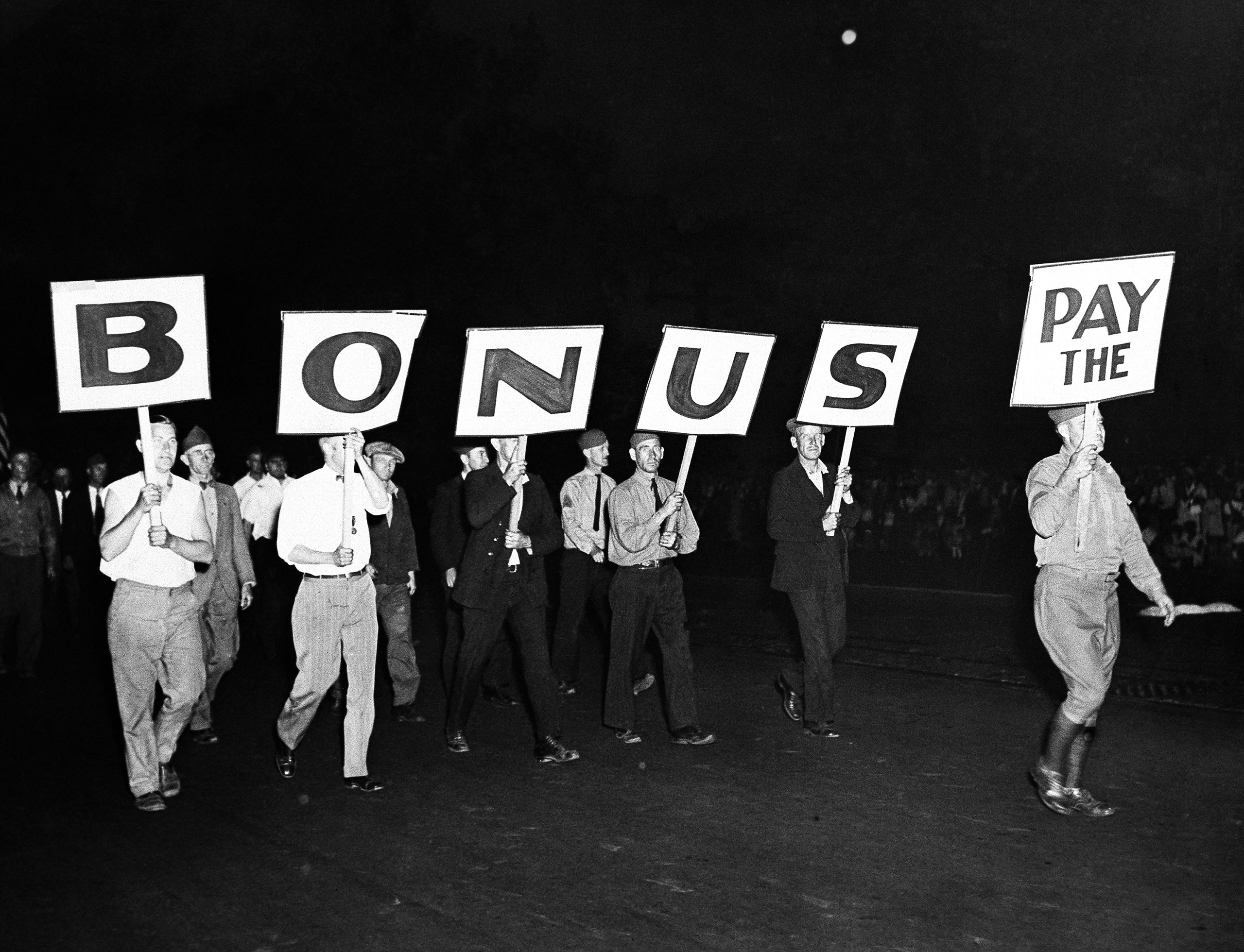 The  Pay The Bonus  sign carried by a group of World War veterans was typical of the banners of the former soldiers who marched to Washington to press their demands for payments of the soldiers' bonus.  June 7, 1932.