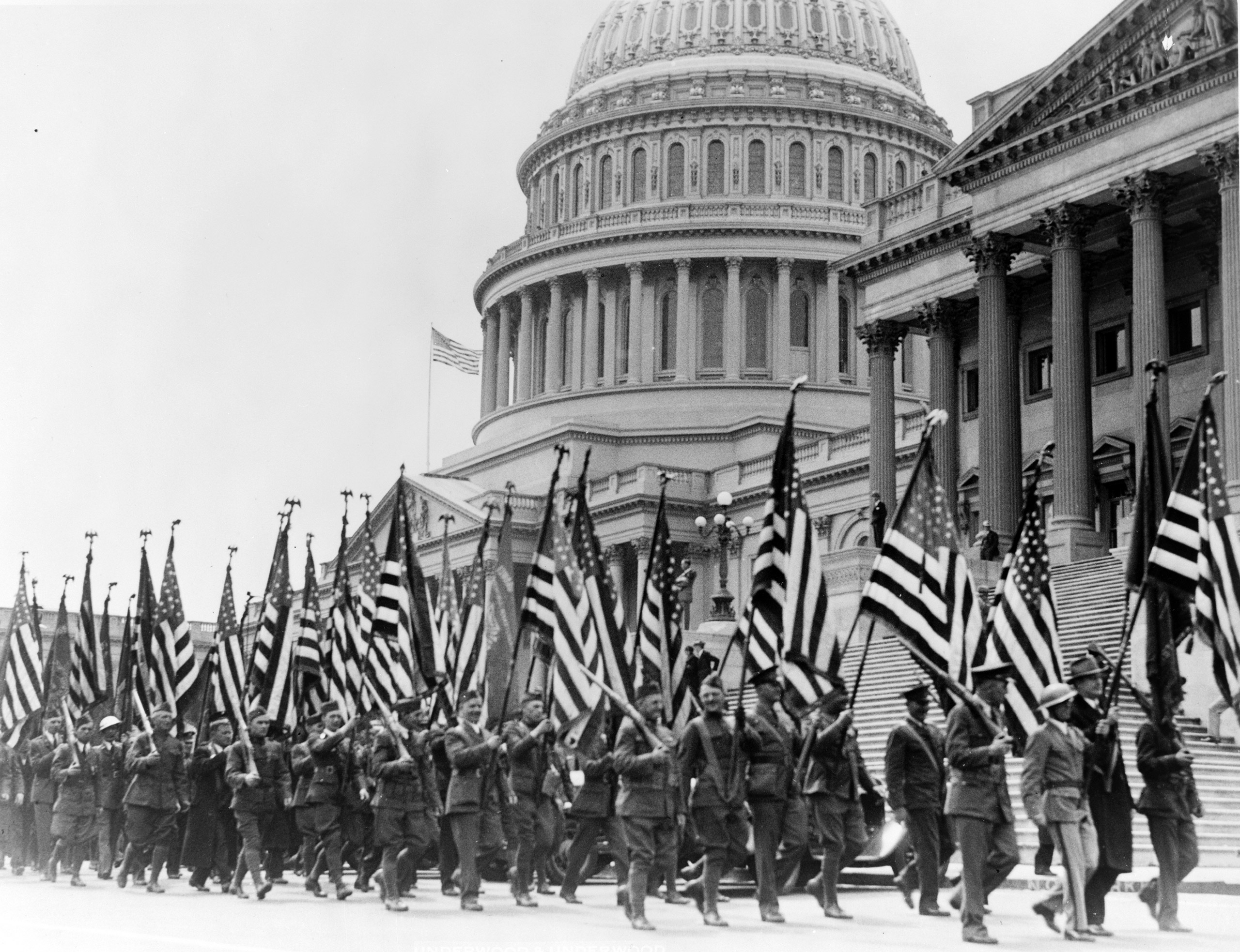 Members of the Bonus Expeditionary Forces, many carrying American flags, marching across the east plaza of the U.S. Capitol. April 8, 1932.
