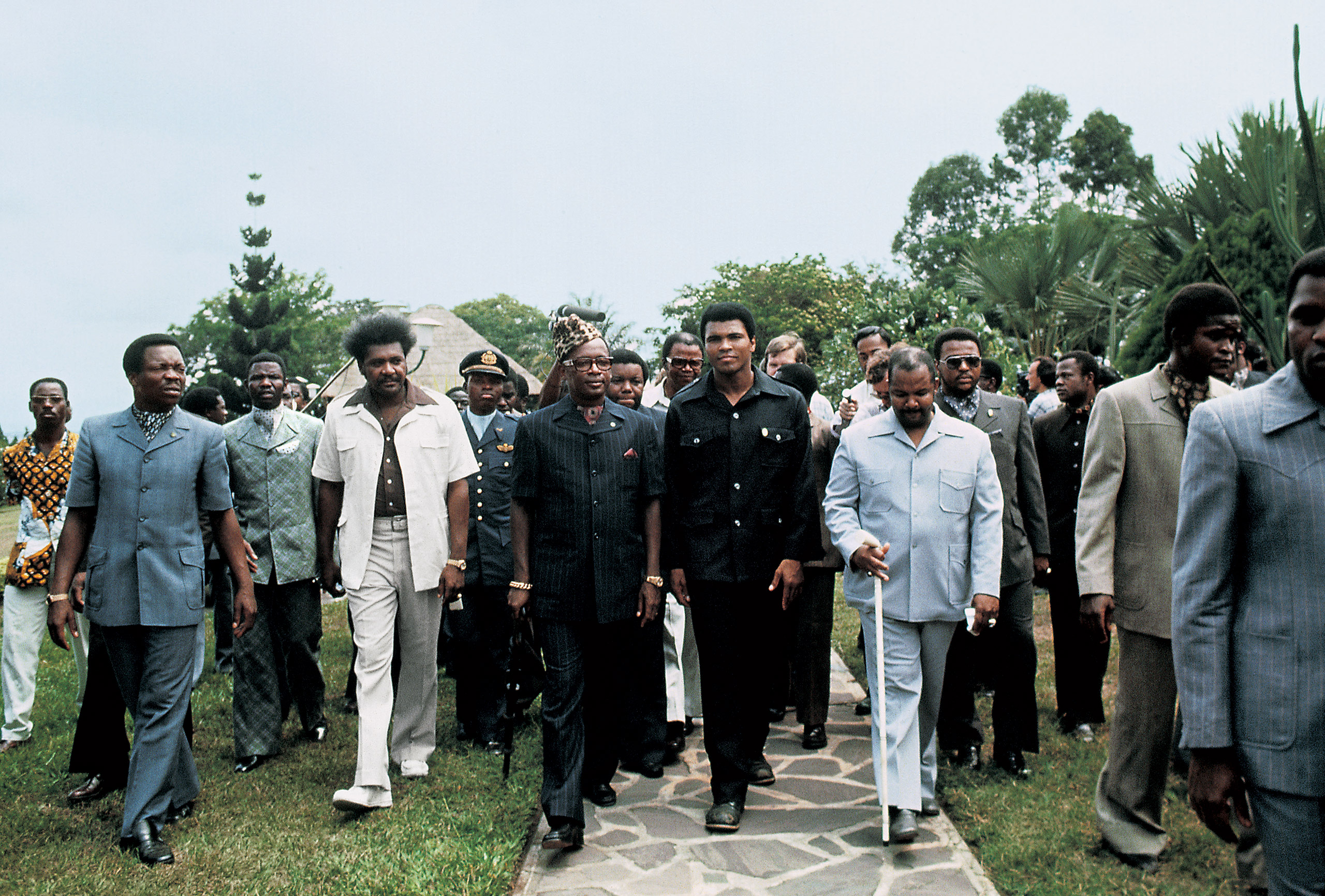 Muhammad Ali, flanked by promoter Don King and his manager Herbert Muhammad, is received by Mobutu Sese Seko,                     president of Zaire, wearing his characteristic leopard-skin hat. The despotic Mobutu readily put up the $10 million combined purse, knowing that the fight would bring Zaire to the international sporting stage.