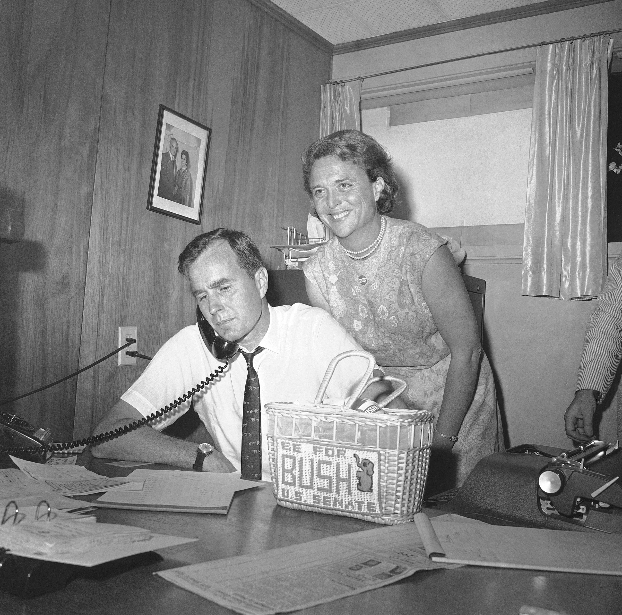 George H.W. Bush, candidate for the Republican nomination for the U.S. Senate, gets returns by phone at his headquarters in Houston, Saturday, June 6, 1964 as his wife Barbara, beams her pleasure at the news.