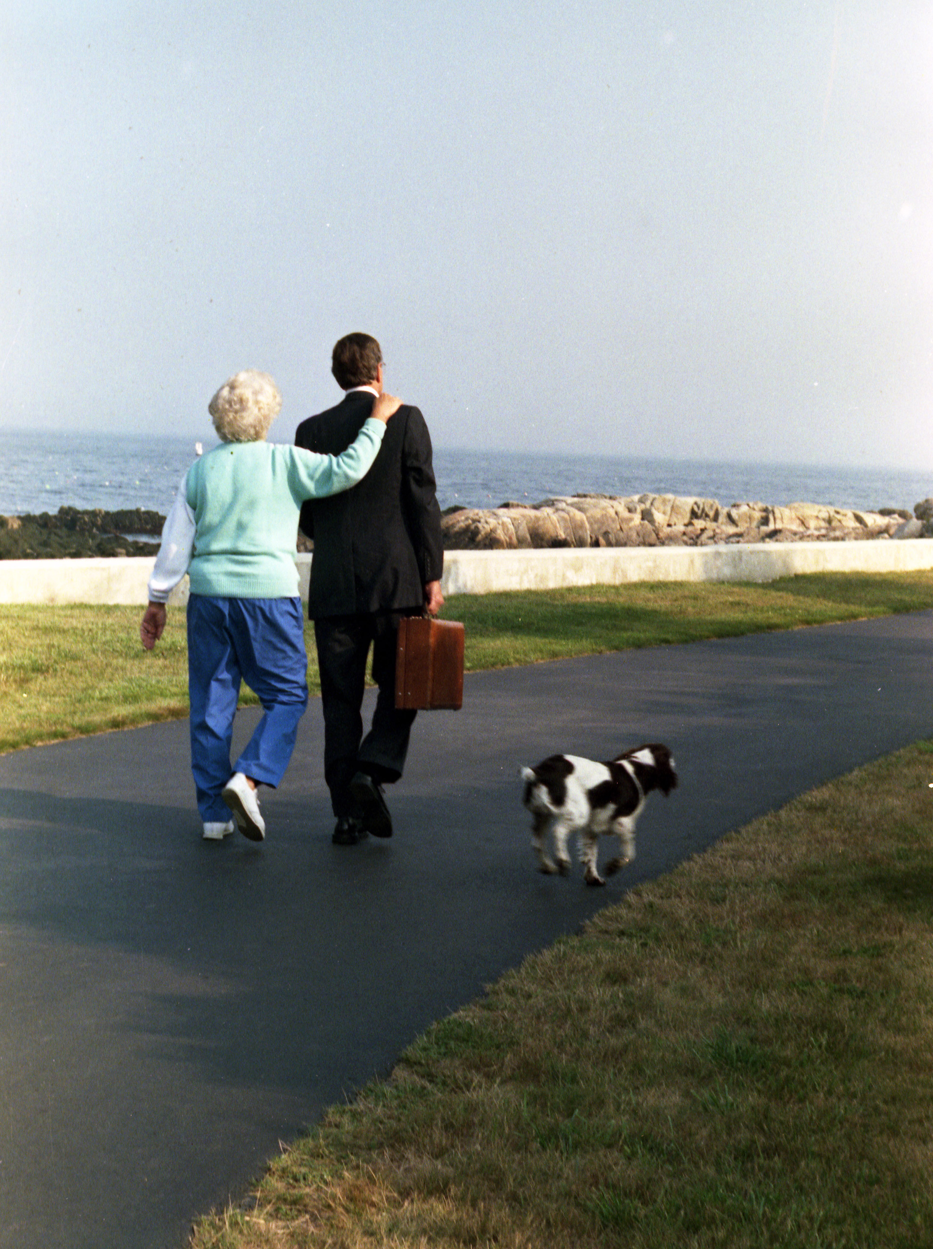 President George H.W. and Mrs. Barbara Bush walk down the driveway as their dog Millie trots alongside, Walker's Point, Kennebunkport, ME, Aug. 16, 1989.