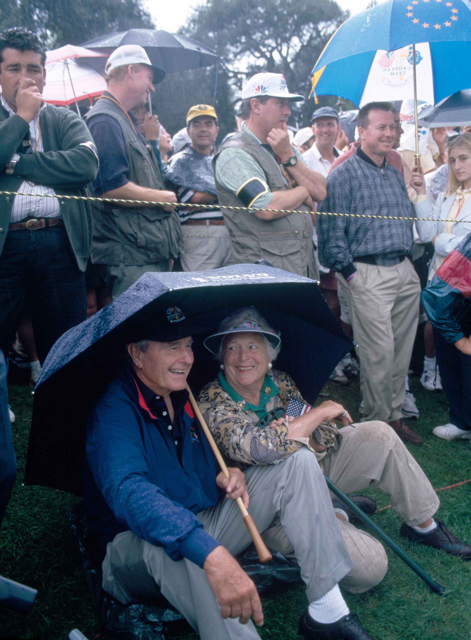 Former President George H.W. Bush and his wife Barbara shelter from the rain during the Ryder Cup golf competition at the Valderrama Golf Club in Sotogrande, Spain, on Sep. 26, 1997.