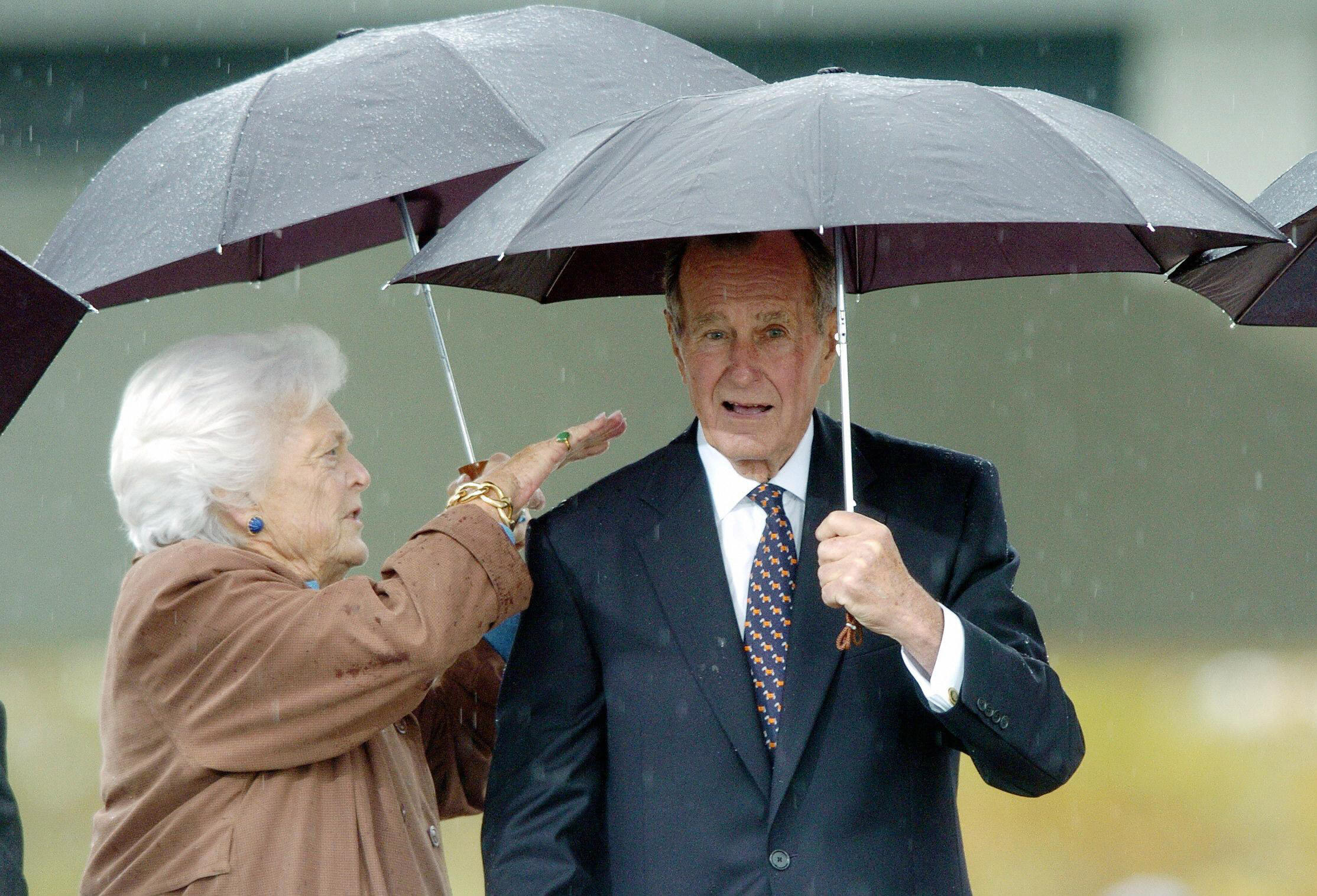 Barbara Bush wipes water off the shoulder of her husband former President George H.W. Bush during the inauguration of the William J. Clinton Presidential Center in Little Rock, Arkansas, on Nov. 18, 2004.