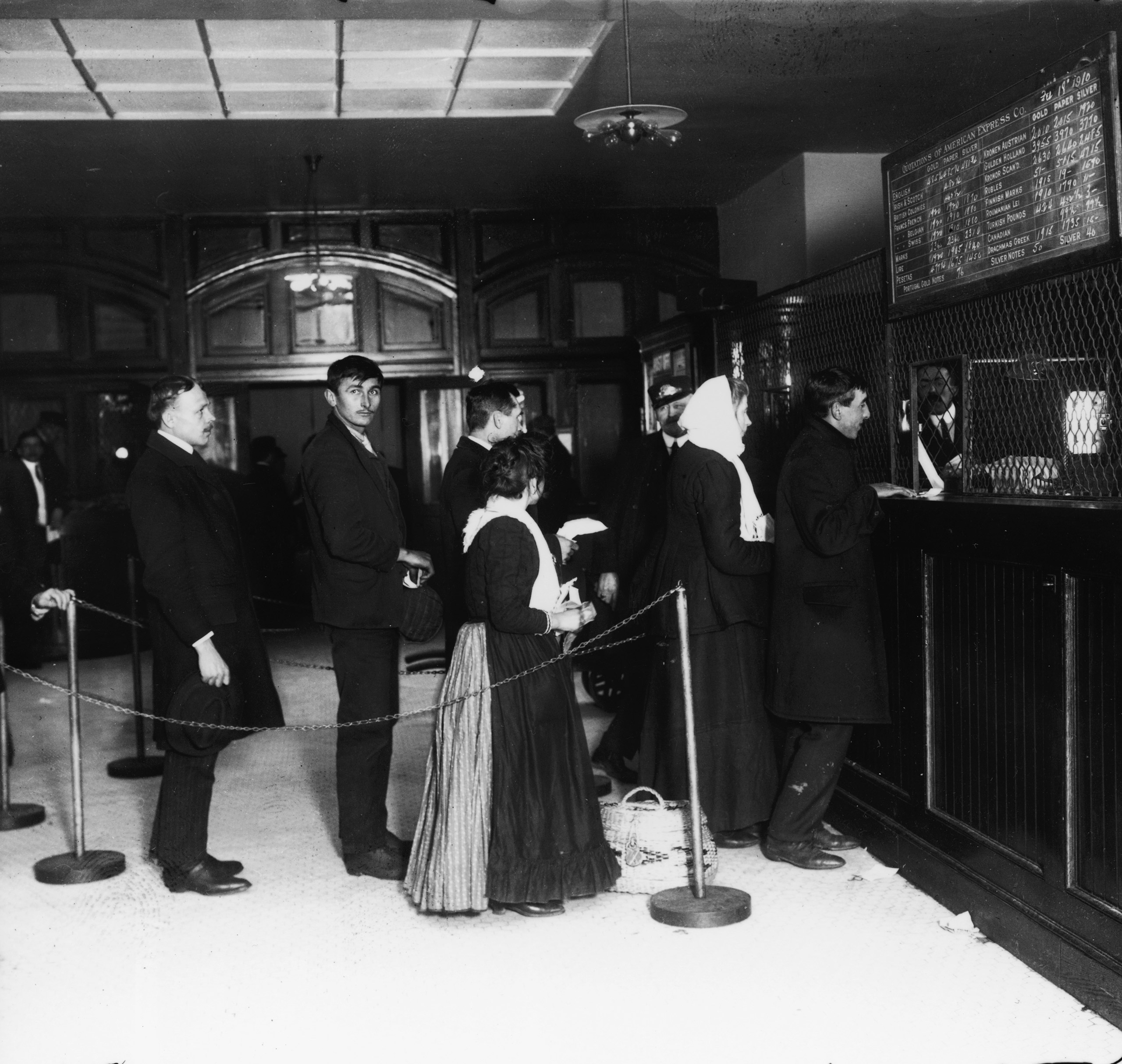 Customers wait in line at a teller's window at a bank on Ellis Island, New York, Feb. 18, 1910.