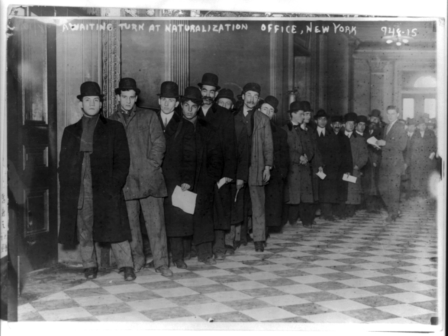 Men standing in line in corridor of naturalization office in New York City, circa 1916.