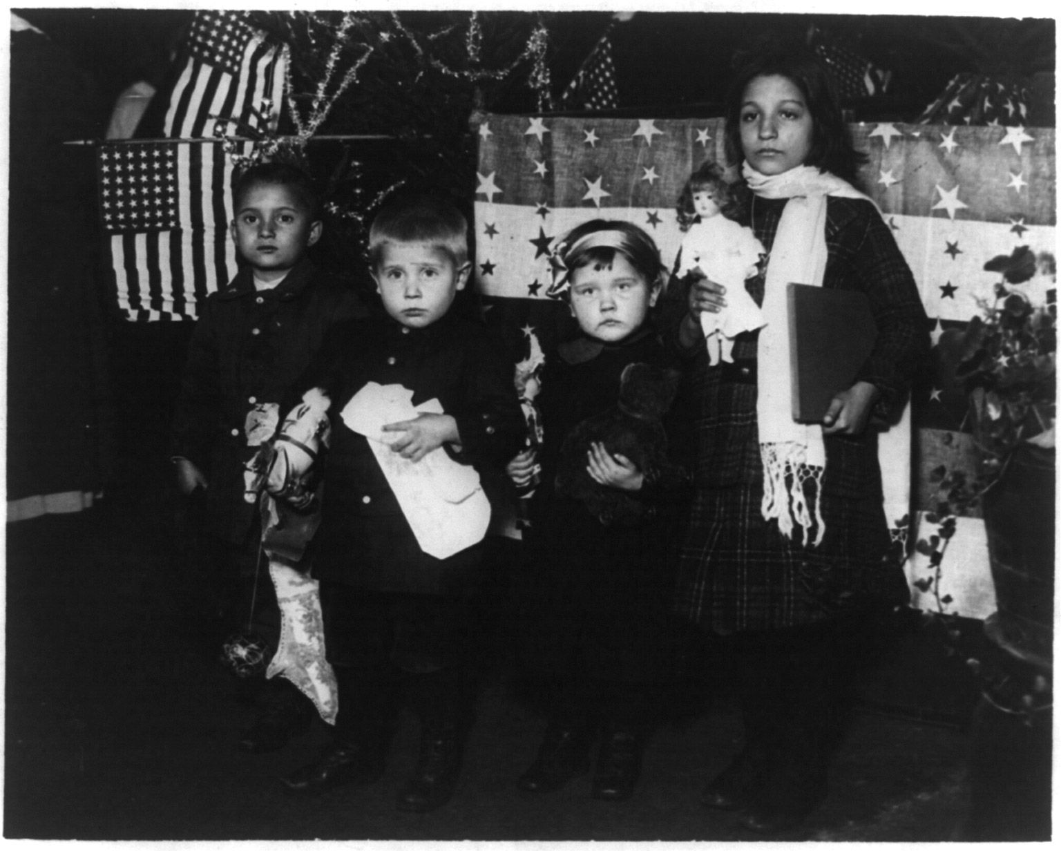 Four immigrant children posed for their first Christmas in America at Ellis Island, circa 1918.