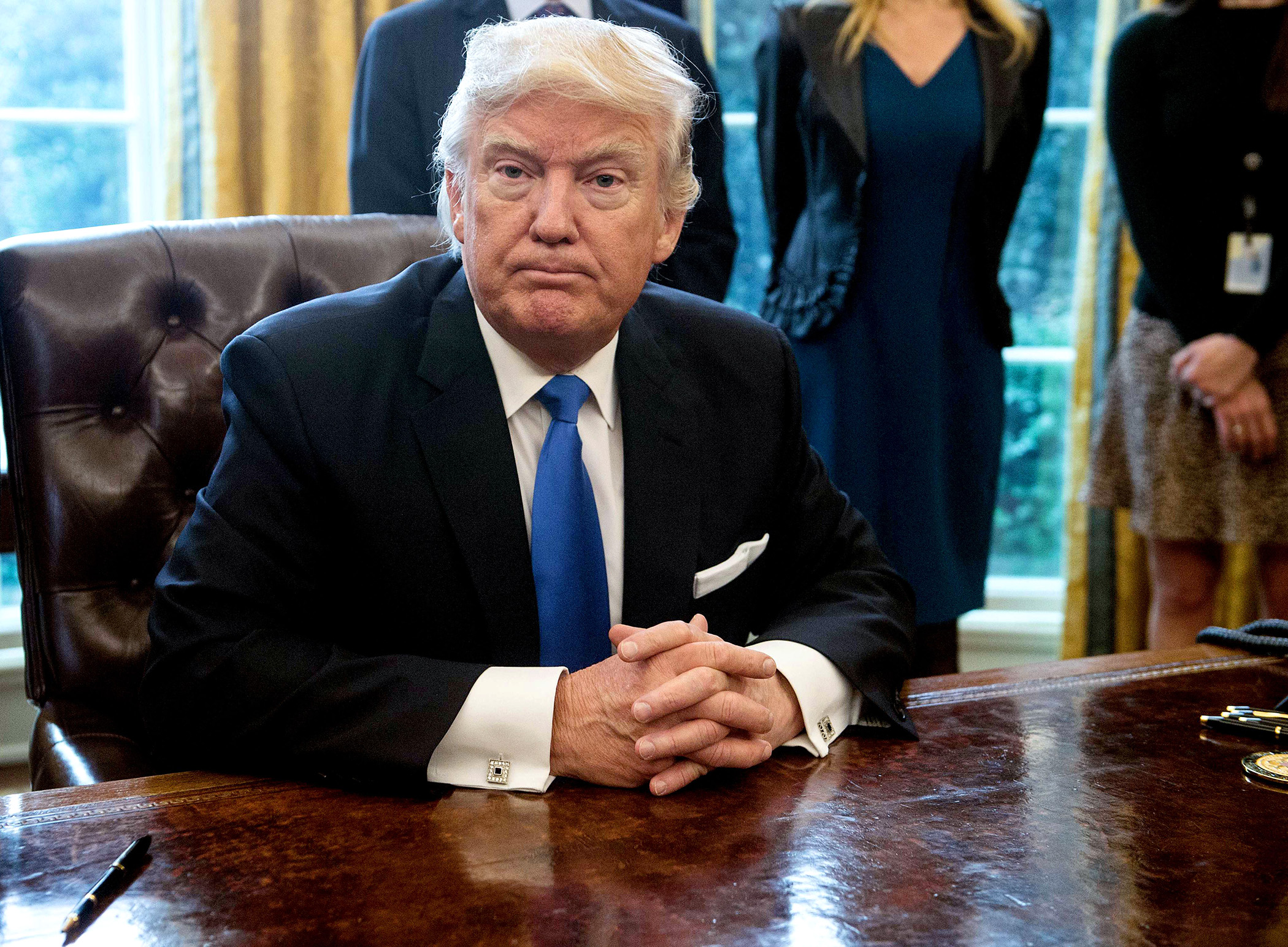 US President Donald Trump looks on after signing executive orders in the Oval Office at the White House in Washington, DC, on January 24, 2017.