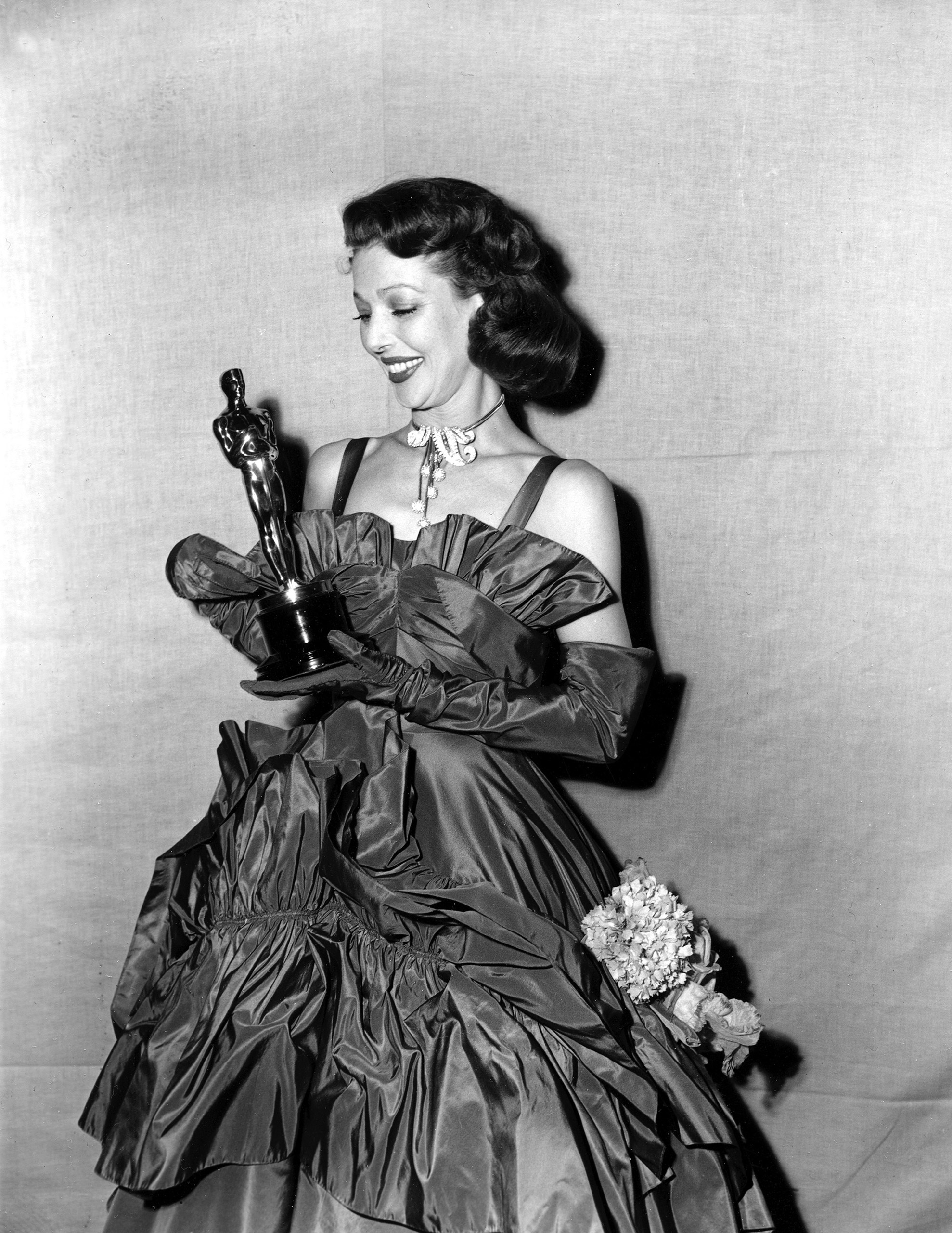 Loretta Young looks at her Oscar at the Academy Awards, 1948.