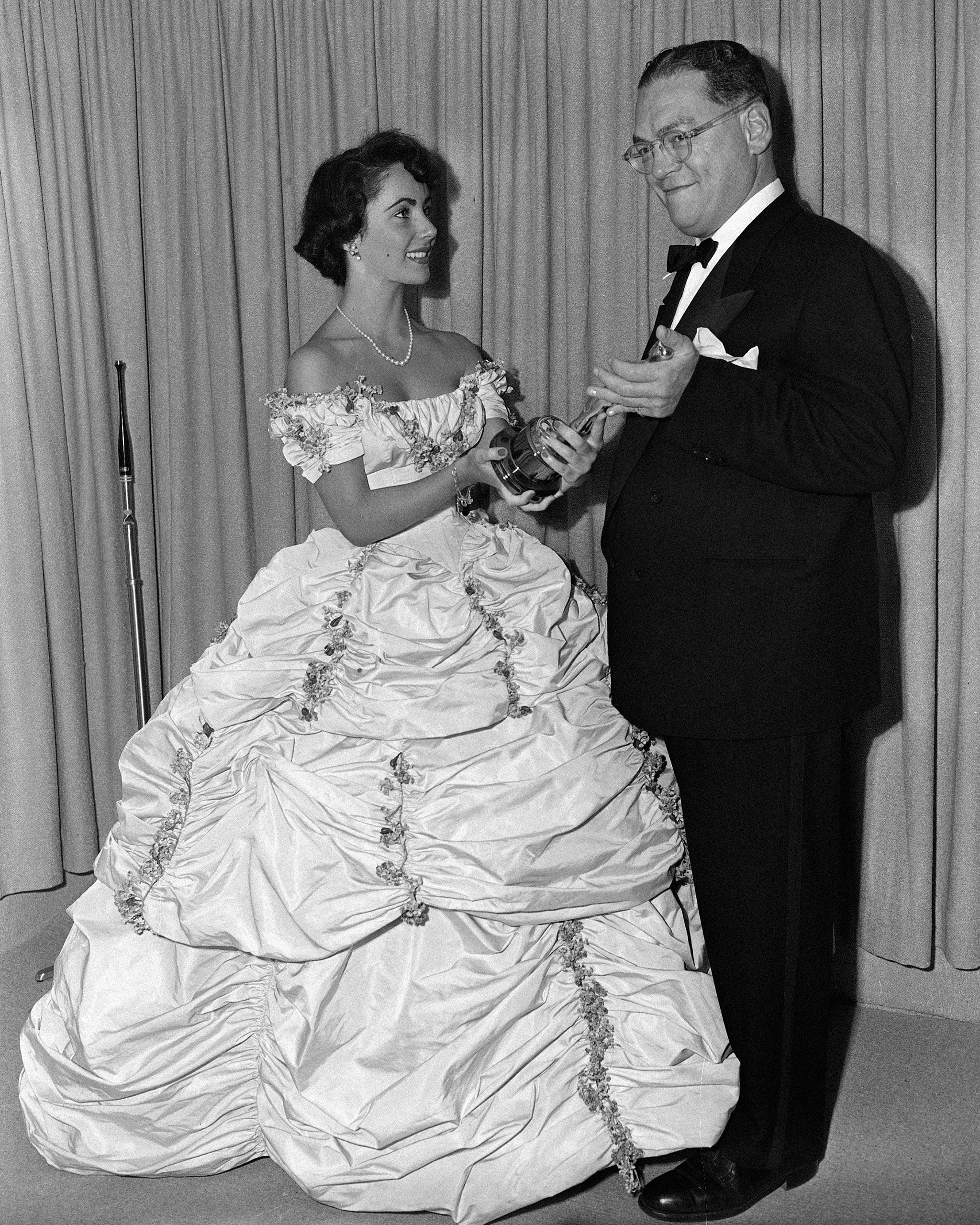 Elizabeth Taylor presents the Oscar for best costumes for black and white films to producer  William Gordon of Universal-International at the Academy Awards, 1949.